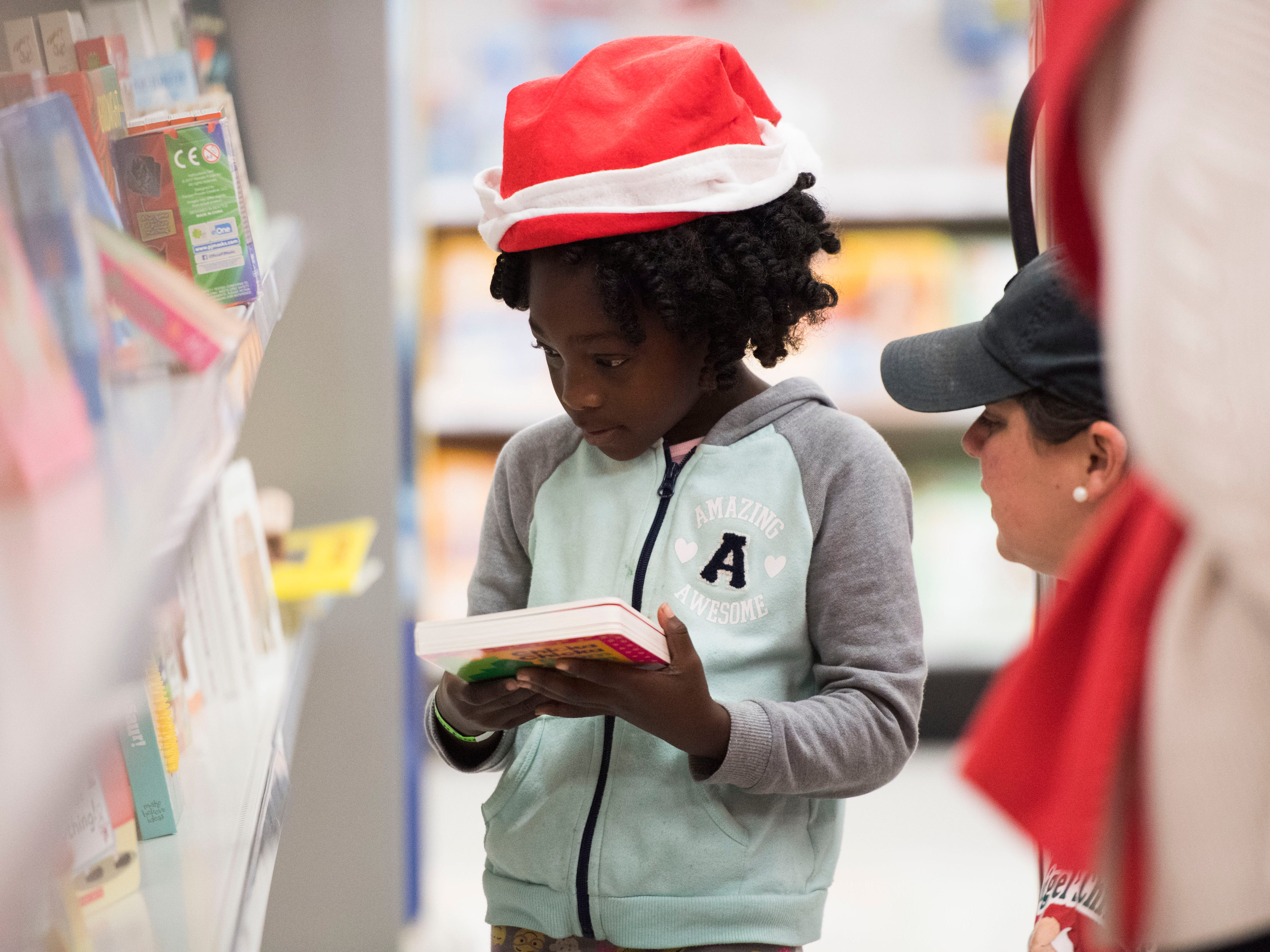 Jah'nae, 6, picks out a book at the Target on Clinton Highway during the annual Weigel's Family Christmas Saturday, Dec. 1, 2018. This is the 21st year Weigel's has held the shopping spree for local underprivileged children.