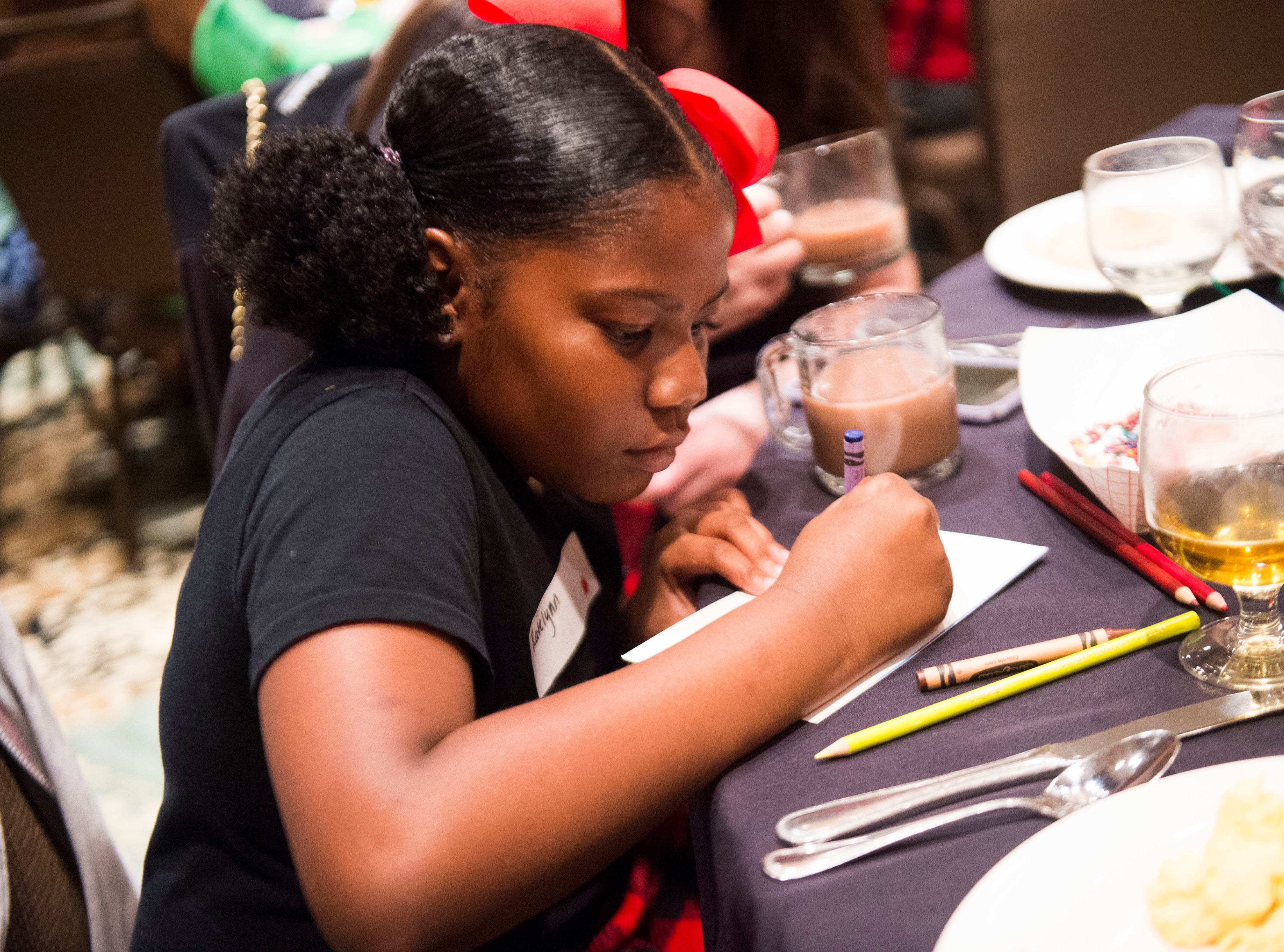 Katelynn Tate, 9, works on a thank you card at Big Brothers Big Sisters annual holiday party at the Crowne Plaza Saturday, Dec. 1, 2018. Nearly 300 mentors, mentees and family members were in attendance.