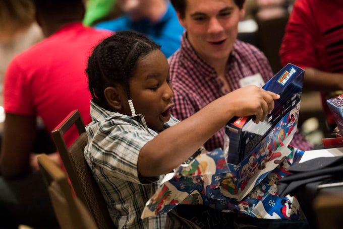 Daylen Robinson, 11, gets excited about his gift at the Big Brothers Big Sisters annual holiday party at the Crowne Plaza Saturday, Dec. 1, 2018. Nearly 300 mentors, mentees and family members were in attendance.