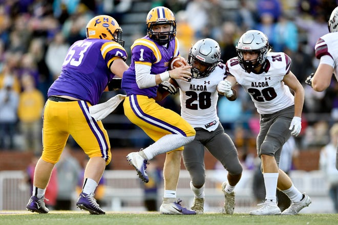 Covington's Brock Lomax (1) tries to evade Alcoa's J.R. Jones (28) and Tyler Boyd (20) during a game between Alcoa and Covington at the TSSAA Blue Cross Bowl at Tennessee Tech's Tucker Stadium in Cookeville, Tennessee on Saturday, December 1, 2018.