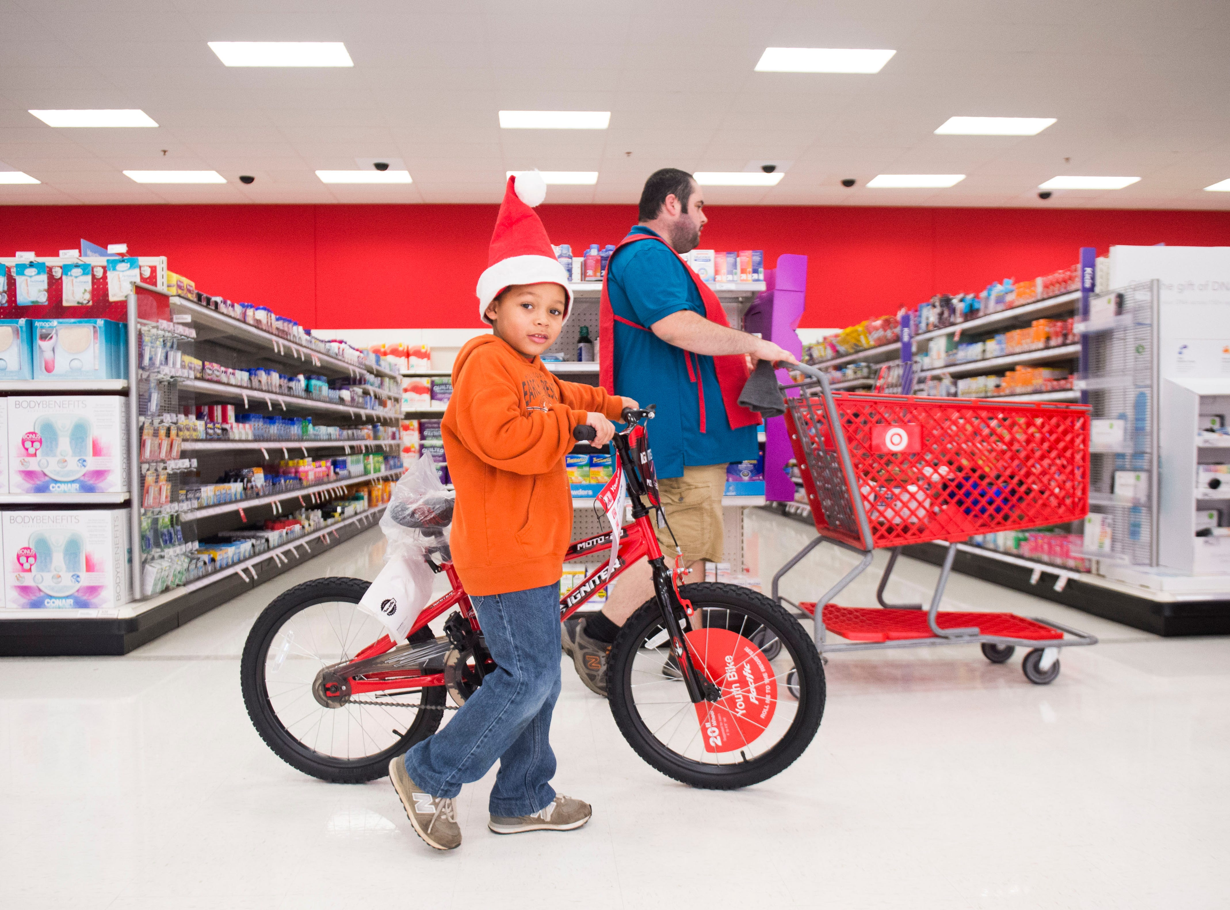 Javontae, 6, pushes his bike towards the cash register at the Target on Clinton Highway during the annual Weigel's Family Christmas Saturday, Dec. 1, 2018. This is the 21st year Weigel's has held the shopping spree for local underprivileged children.