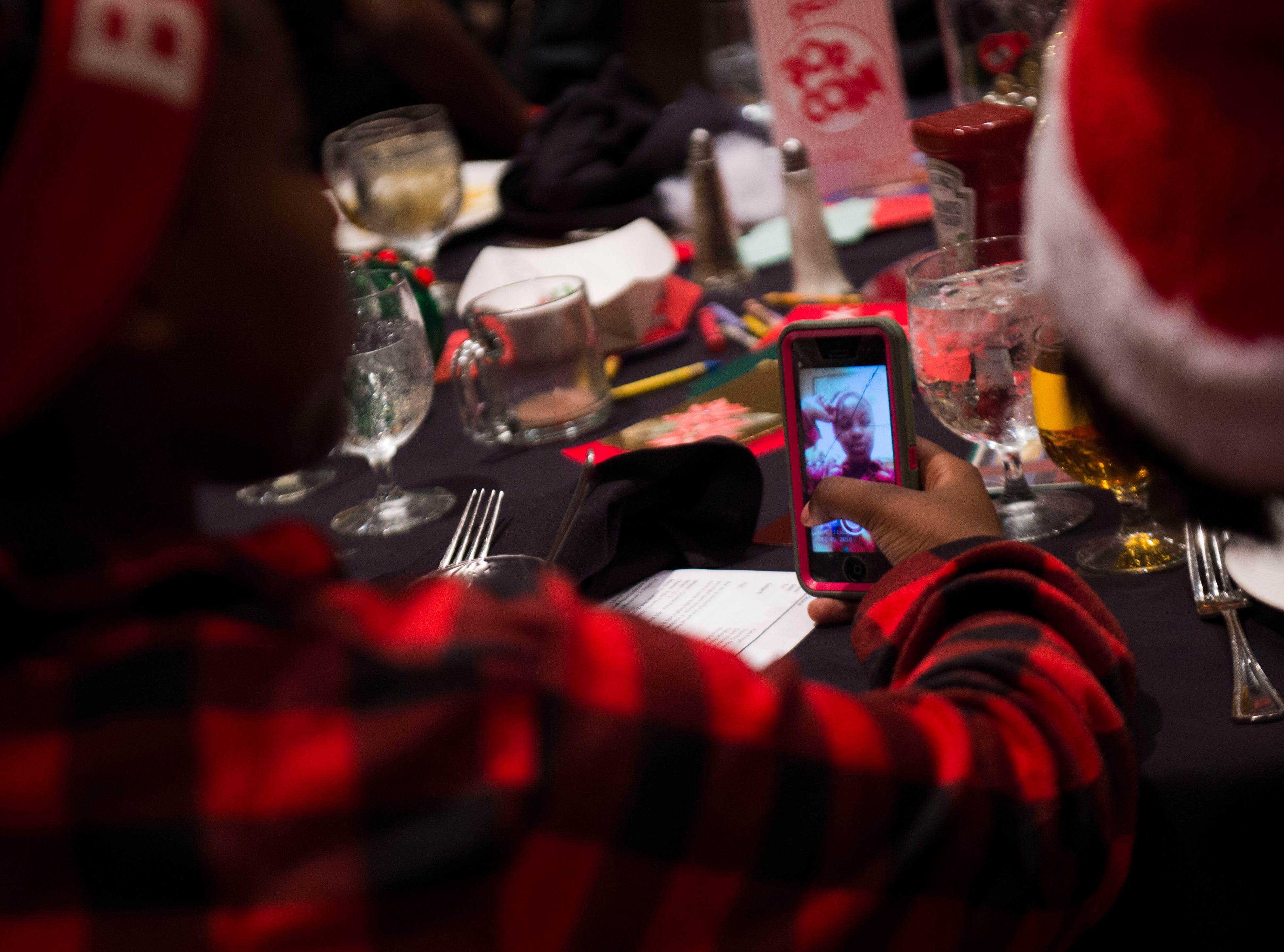 Maria Nshimirimana, 13, takes a selfie at the Big Brothers Big Sisters annual holiday party at the Crowne Plaza Saturday, Dec. 1, 2018. Nearly 300 mentors, mentees and family members were in attendance.