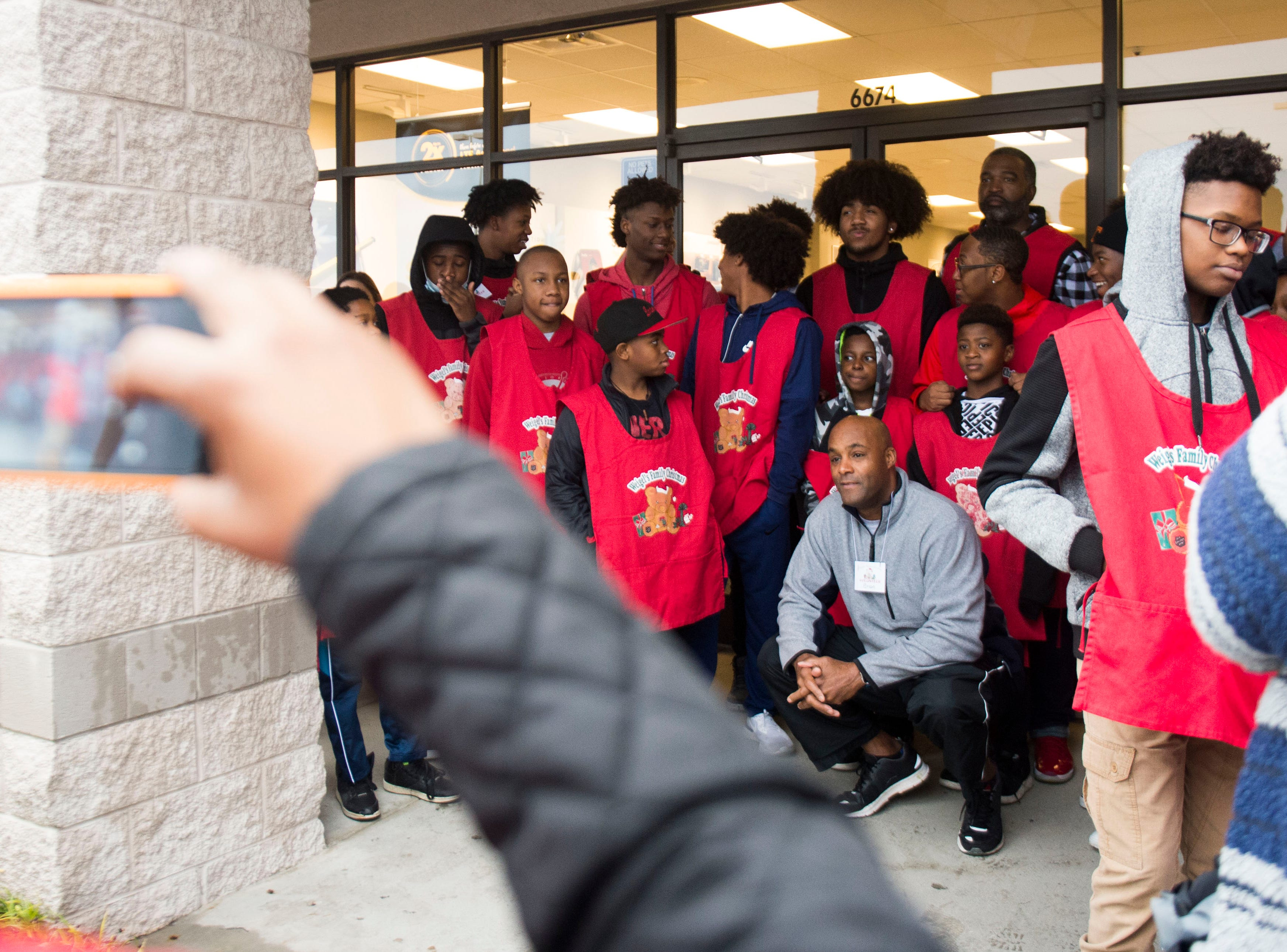 Members of 100 Black Men pose for a photo while waiting for children to arrive on buses at the Target on Clinton Highway during the annual Weigel's Family Christmas Saturday, Dec. 1, 2018. This is the 21st year Weigel's has held the shopping spree for local underprivileged children.