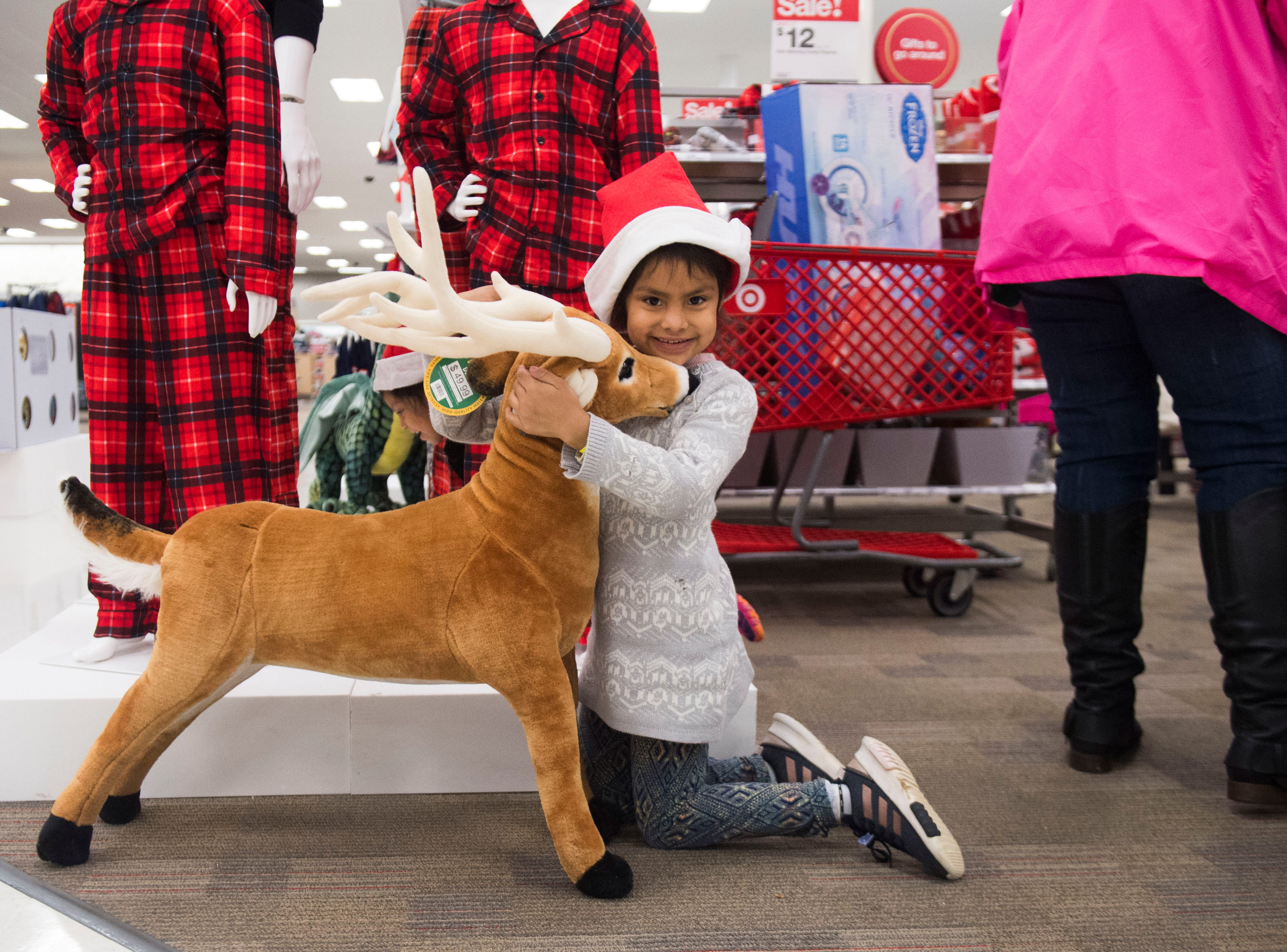 Alondra, 5, poses for a photo with a reindeer at the Target on Clinton Highway during the annual Weigel's Family Christmas Saturday, Dec. 1, 2018. This is the 21st year Weigel's has held the shopping spree for local underprivileged children.