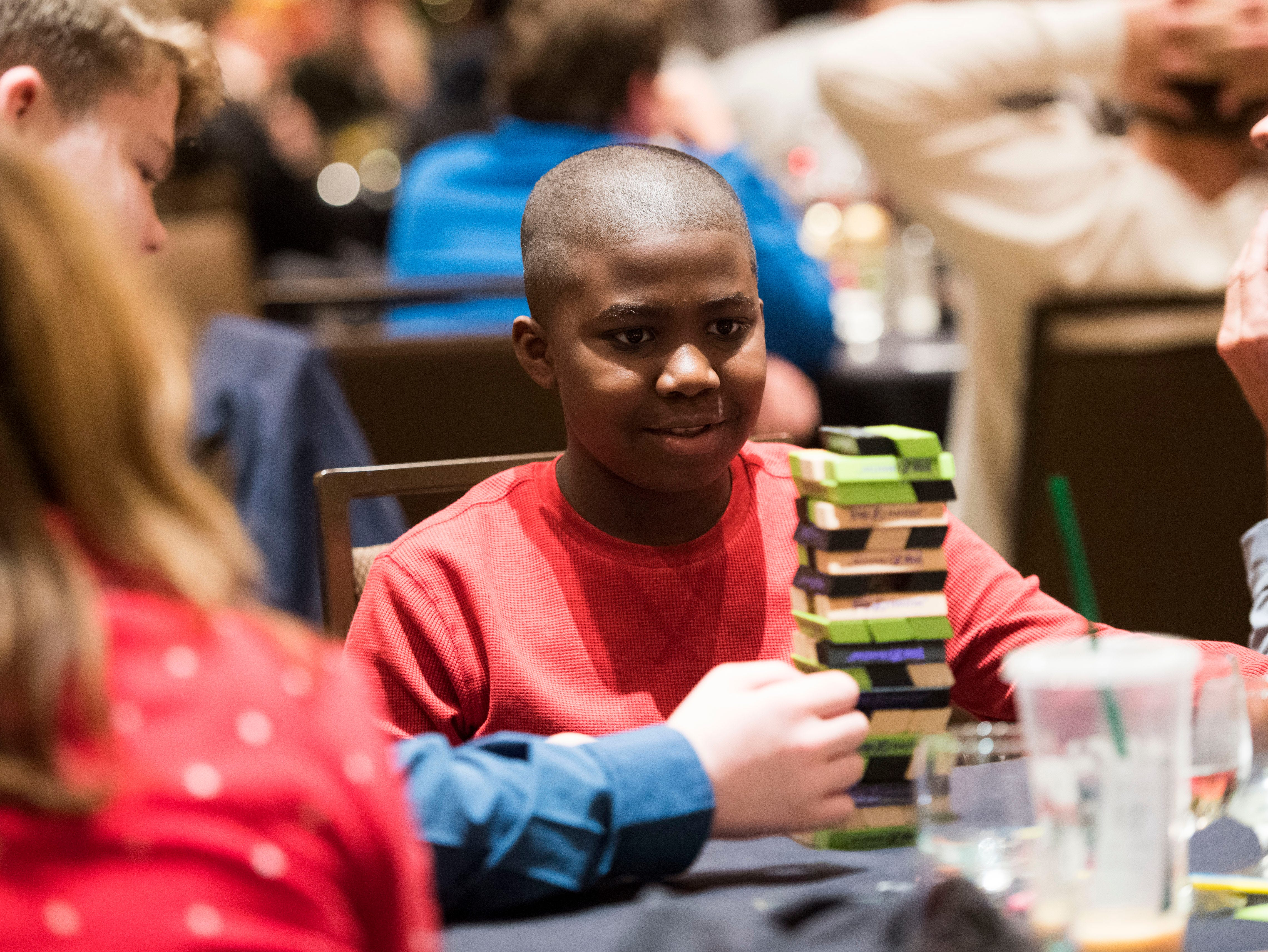 Coryion Downs, 11, plays Jenga at the Big Brothers Big Sisters annual holiday party at the Crowne Plaza Saturday, Dec. 1, 2018. Nearly 300 mentors, mentees and family members were in attendance.