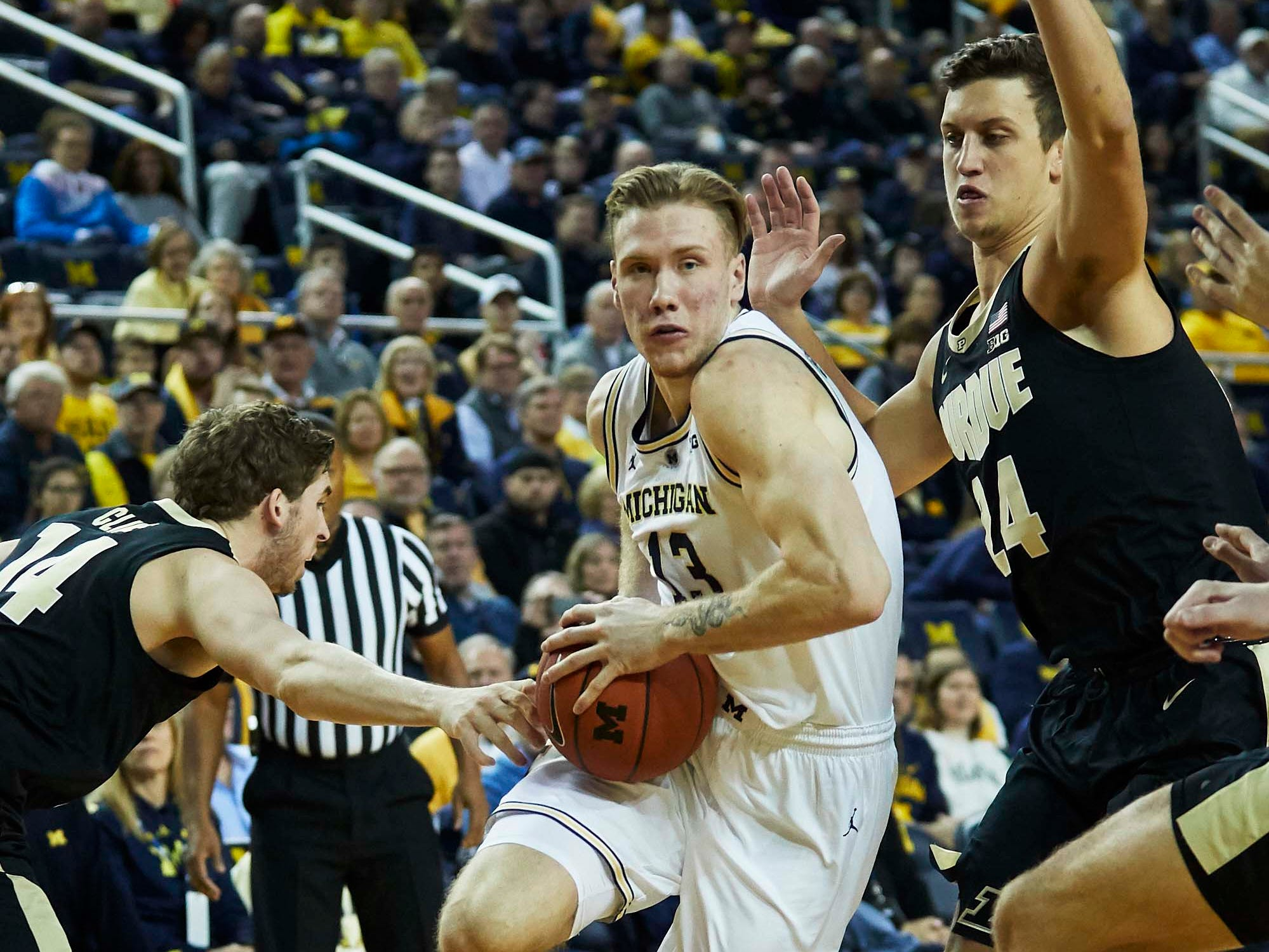 Dec 1, 2018; Ann Arbor, MI, USA; Michigan Wolverines forward Ignas Brazdeikis (13) dribbles on Purdue Boilermakers guard Ryan Cline (14) and forward Grady Eifert (24) in the first half at Crisler Center. Mandatory Credit: Rick Osentoski-USA TODAY Sports