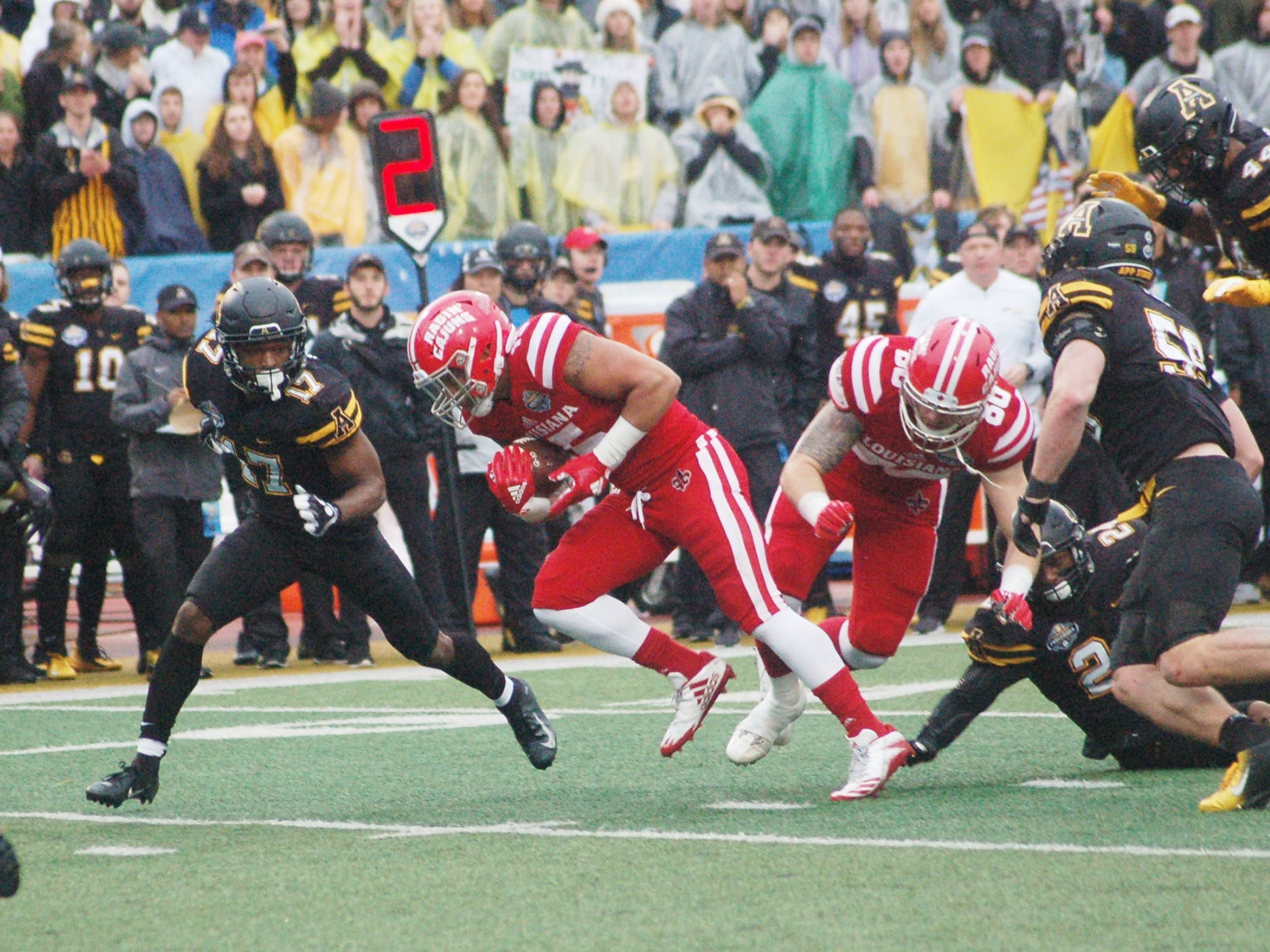 UL running back Elijah Mitchell runs through the Appalachian State defensive line as Tae Hayes closes in to make the tackle Saturday in the Sun Belt Conference Championship Game in Boone, North Carolina.