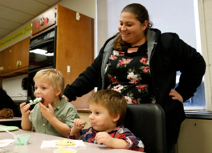 Jennifer Stevens, from Pleasantville, laughs as she watches her sons Carter Stevens, 4, left, and Finn Stevens, 2, eat in the cookie decorating station Saturday, Dec. 1, 2018, at the Gift of Time at Lancaster High School in Lancaster. The annual free community event featured activities from children younger than 8 and their families. More than 20 community organizations provided stations ranging from cookie decorating, story book reading, gift bag decoration and photographs with Santa Claus.