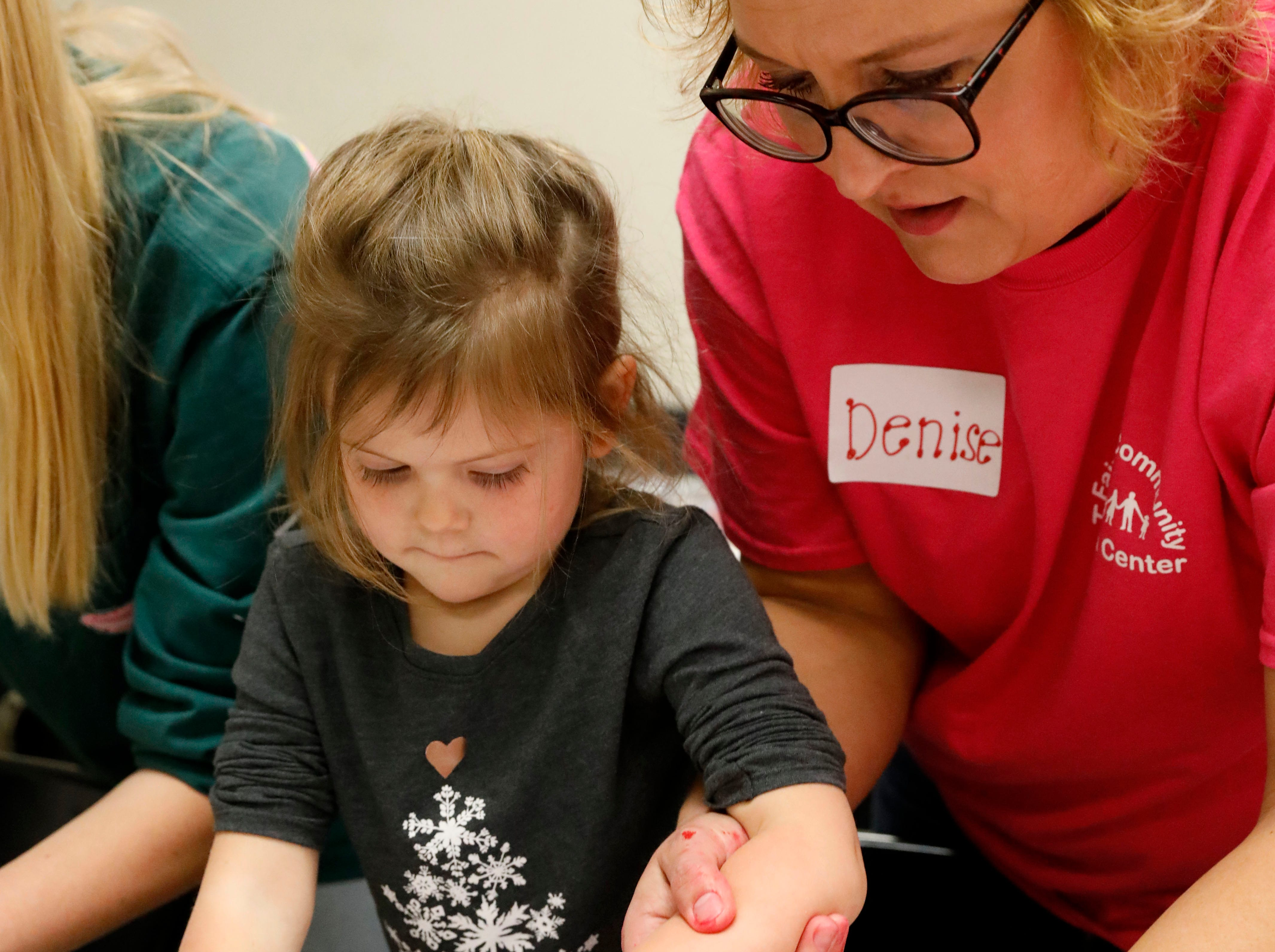Denise Ream, right, helps Kinsley Taylor, 3, make a hand print on a piece of paper Saturday, Dec. 1, 2018, at the Gift of Time event at Lancaster High School in Lancaster. Volunteers turned the red hand print into a cardinal as children visited other stations at the annual free community event.
