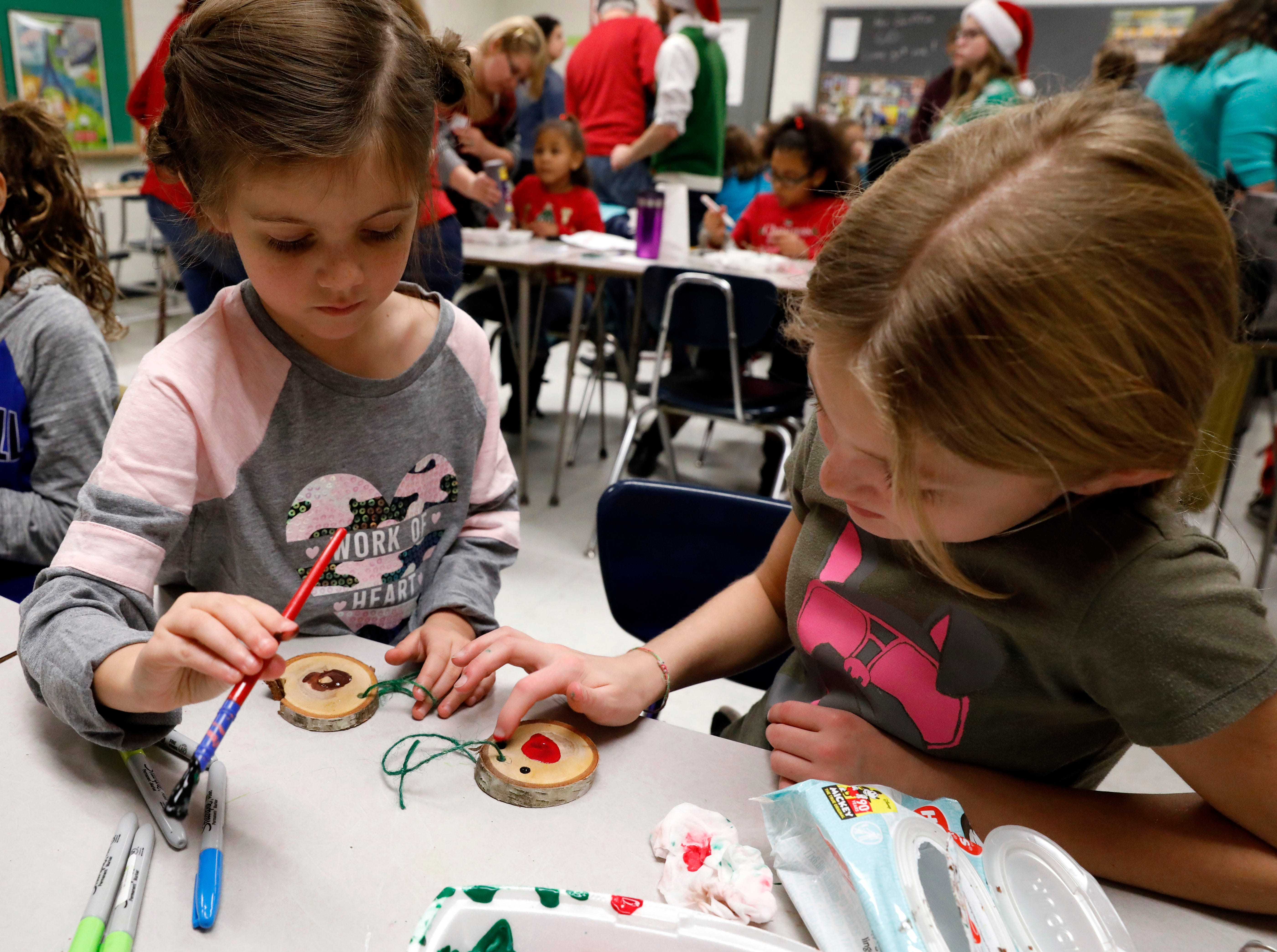 Joss Roinette, 7, left, and Cruz Short, 10, paint wooden Christmas ornaments Saturday afternoon, Dec. 1, 2018, during the annual Gift of Time free community event at Lancaster High School in Lancaster.