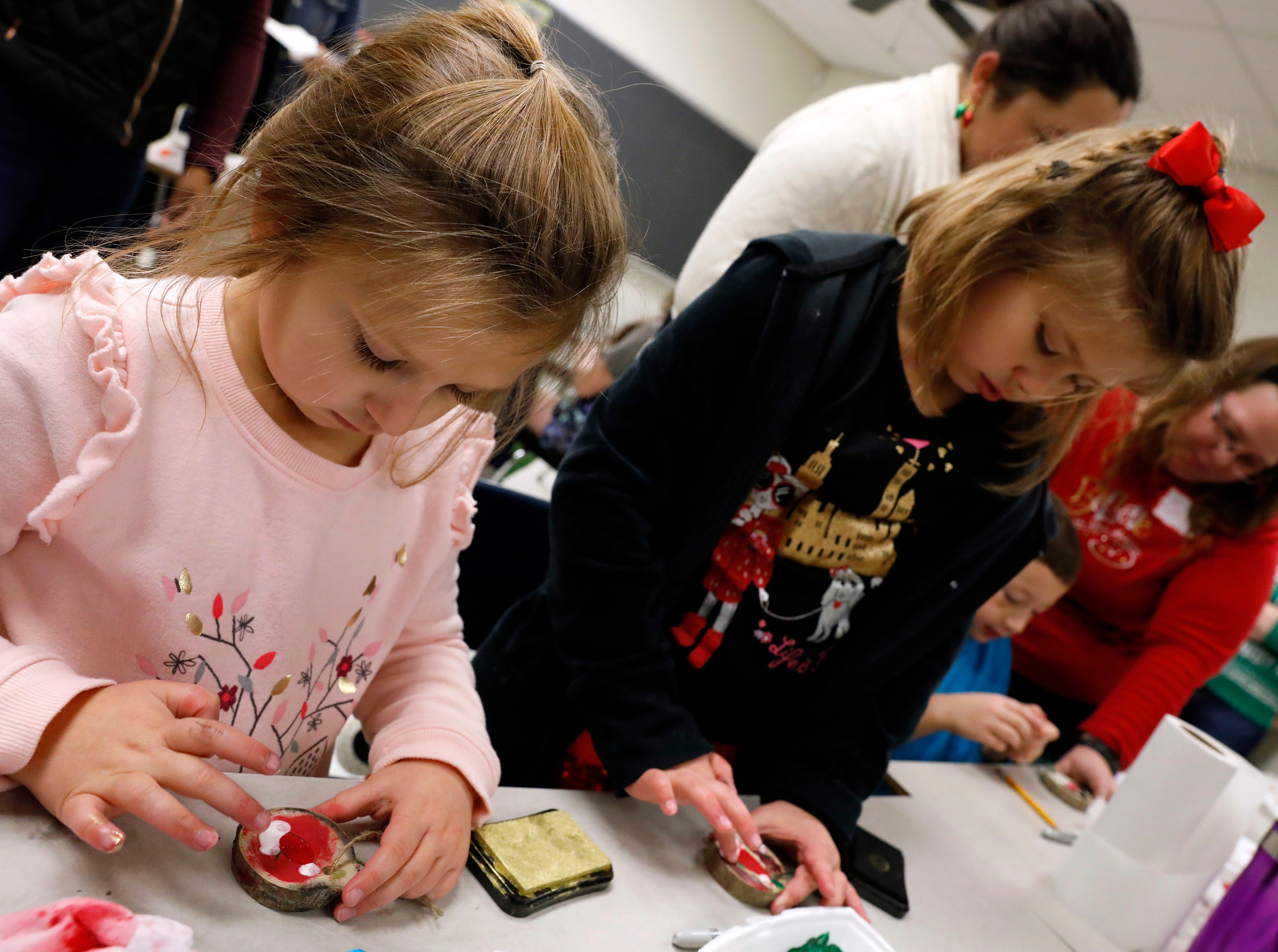 Alexis Beavers, 7, left, and Rosealeigh Marteney, 6, finger paint wooden Christmas ornaments Saturday afternoon, Dec. 1, 2018, during the annual Gift of Time free community event at Lancaster High School in Lancaster.