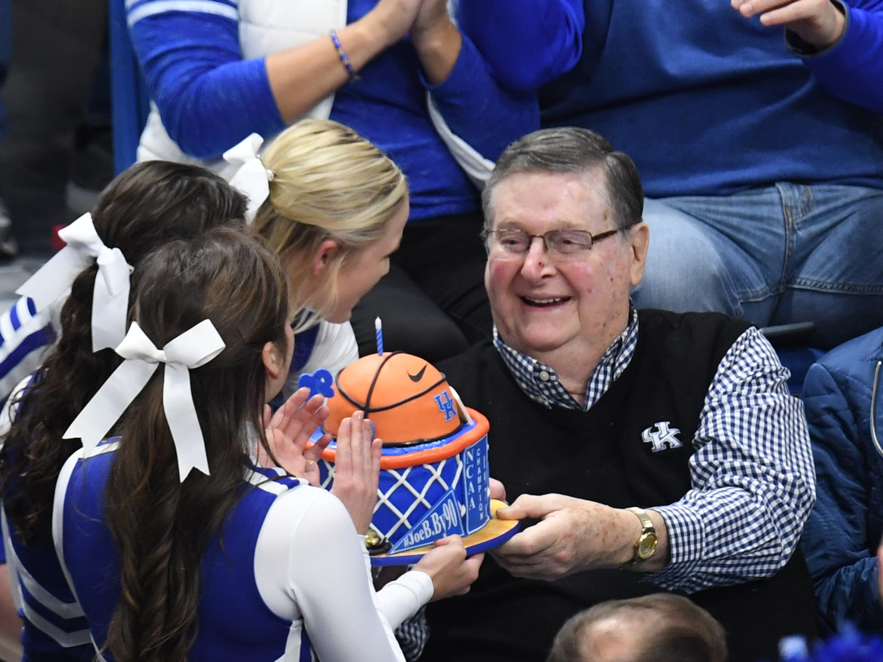 Former UK head coach Joe B. Hall celebrates his 90th birthday and is presented a cake by UK cheerleaders during the University of Kentucky men's basketball game against UNC Greensboro at Rupp Arena in Lexington, Kentucky on Saturday, December 1, 2018.