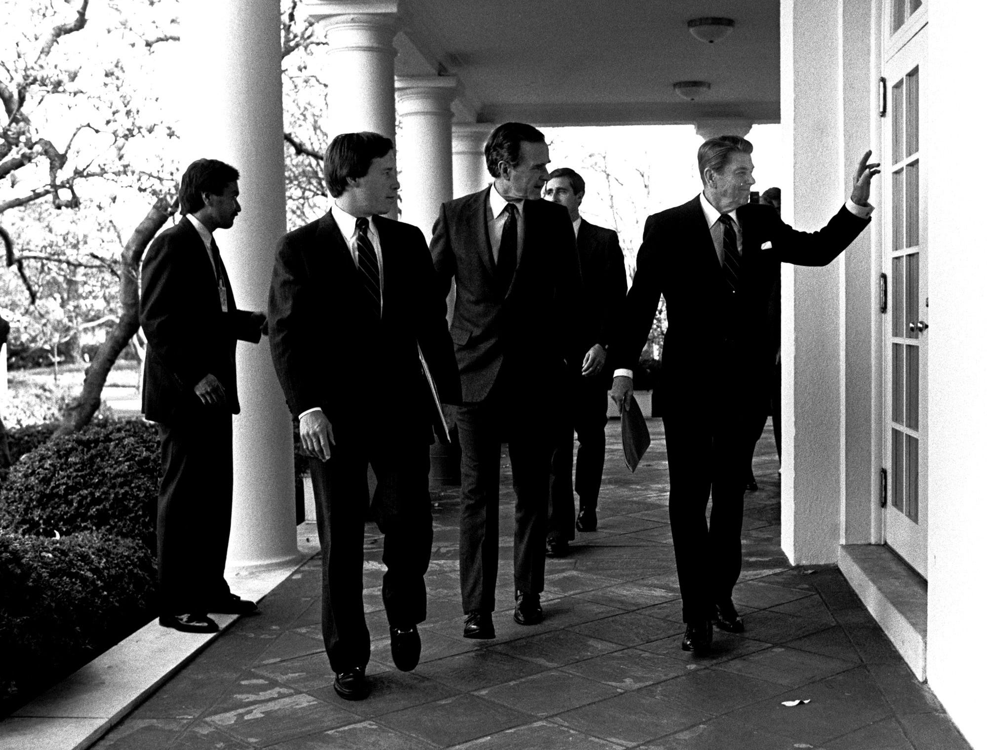 President Reagan waves to a staffer while walking with Vice-President Bush at the White House, April, 1985.