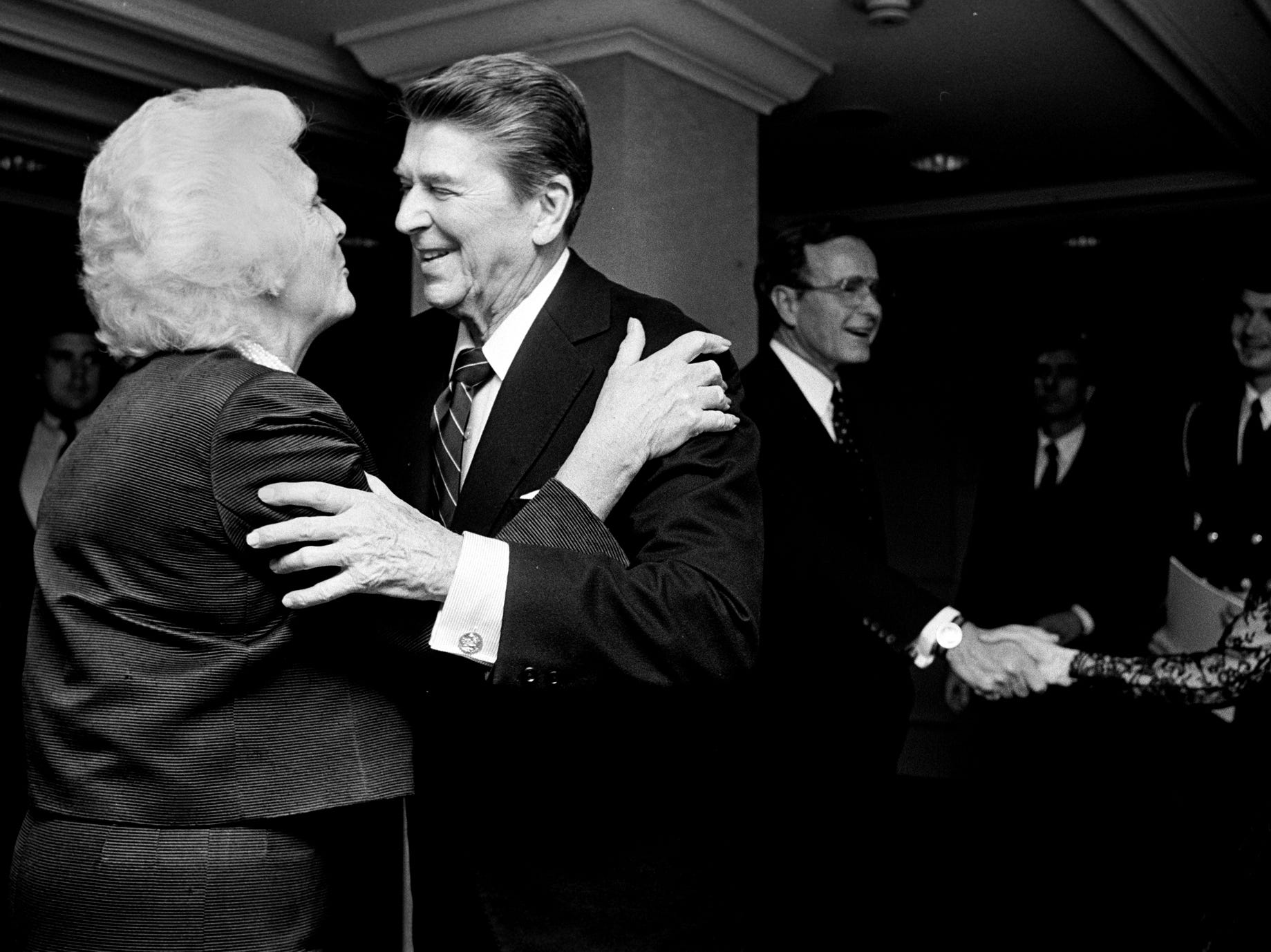 President Reagan talks with Barbara Bush, left, as Vice-President George H. W. Bush shakes hands with Ms. Nancy Reagan at an event in 1985.(By Bill Luster, The Courier-Journal)