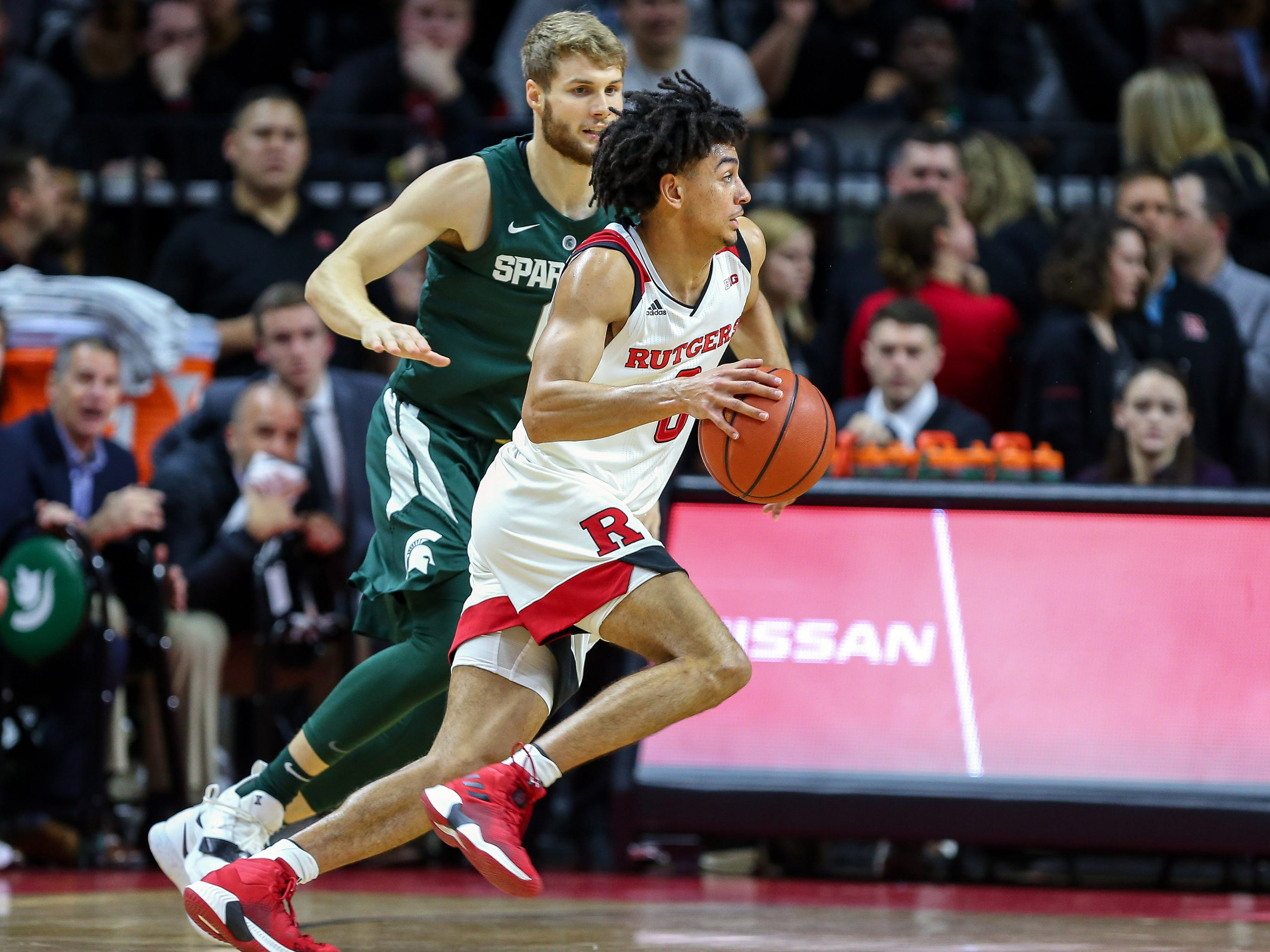 Rutgers Scarlet Knights guard Geo Baker (0) drives to the basket in front of Michigan State Spartans forward Kyle Ahrens (0) during the first half at Rutgers Athletic Center (RAC).