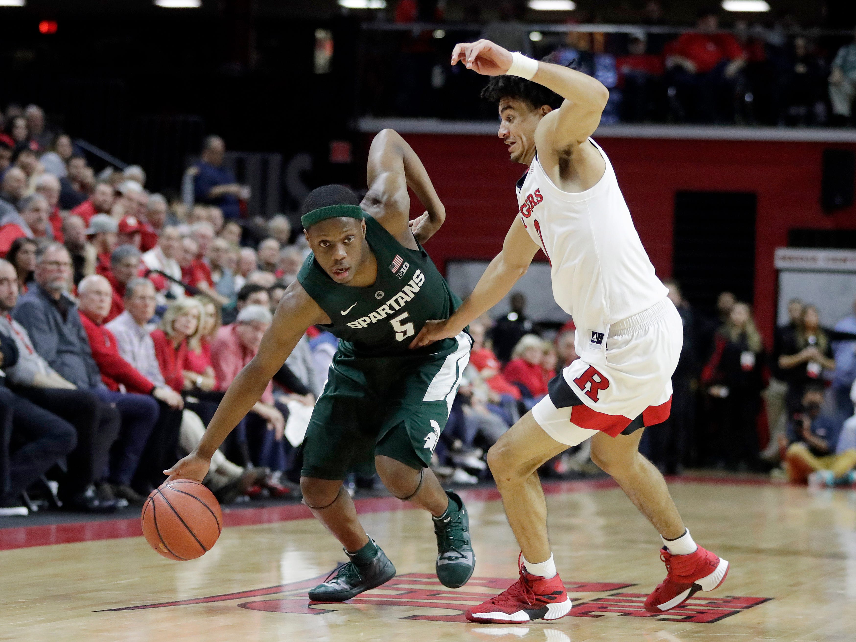 Michigan State guard Cassius Winston (5) drives against Rutgers guard Geo Baker during the second half of an NCAA college basketball game, Friday, Nov. 30, 2018, in Piscataway, N.J.