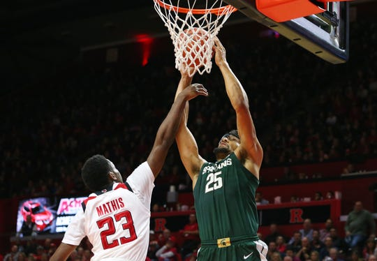 Kenny Goins #25 of the Michigan State Spartans attempts a shot as Montez Mathis #23 of the Rutgers Scarlet Knights defends during the first half of a college basketball game at the Rutgers Athletic Center on November 30, 2018 in Piscataway, New Jersey. Michigan State defeated Rutgers 78-67.