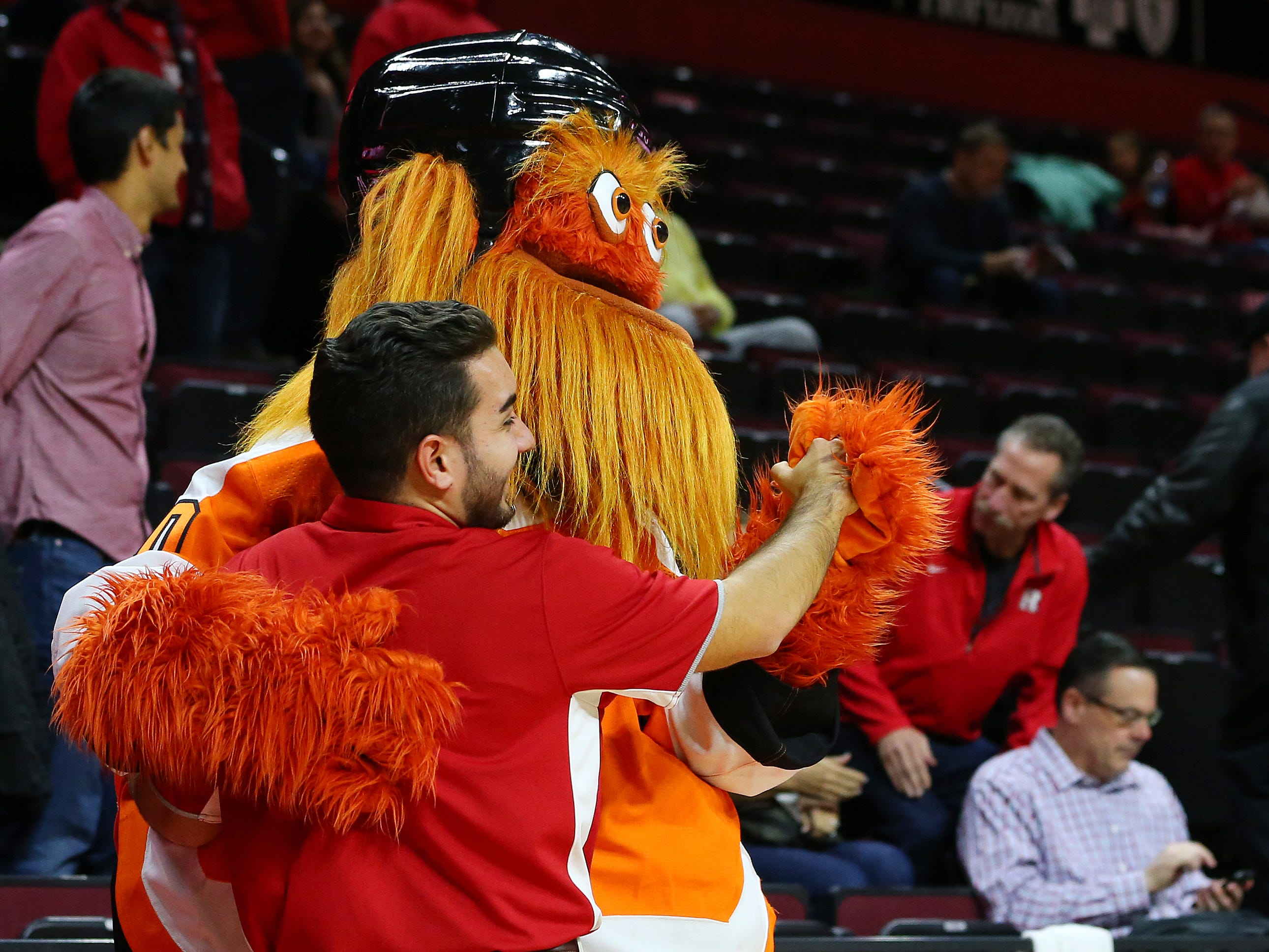 Gritty, the mascot of the Philadelphia Flyers NHL hockey team, dances with an usher before a college basketball game between the Michigan State Spartans and Rutgers Scarlet Knights at the Rutgers Athletic Center on November 30, 2018 in Piscataway, New Jersey.