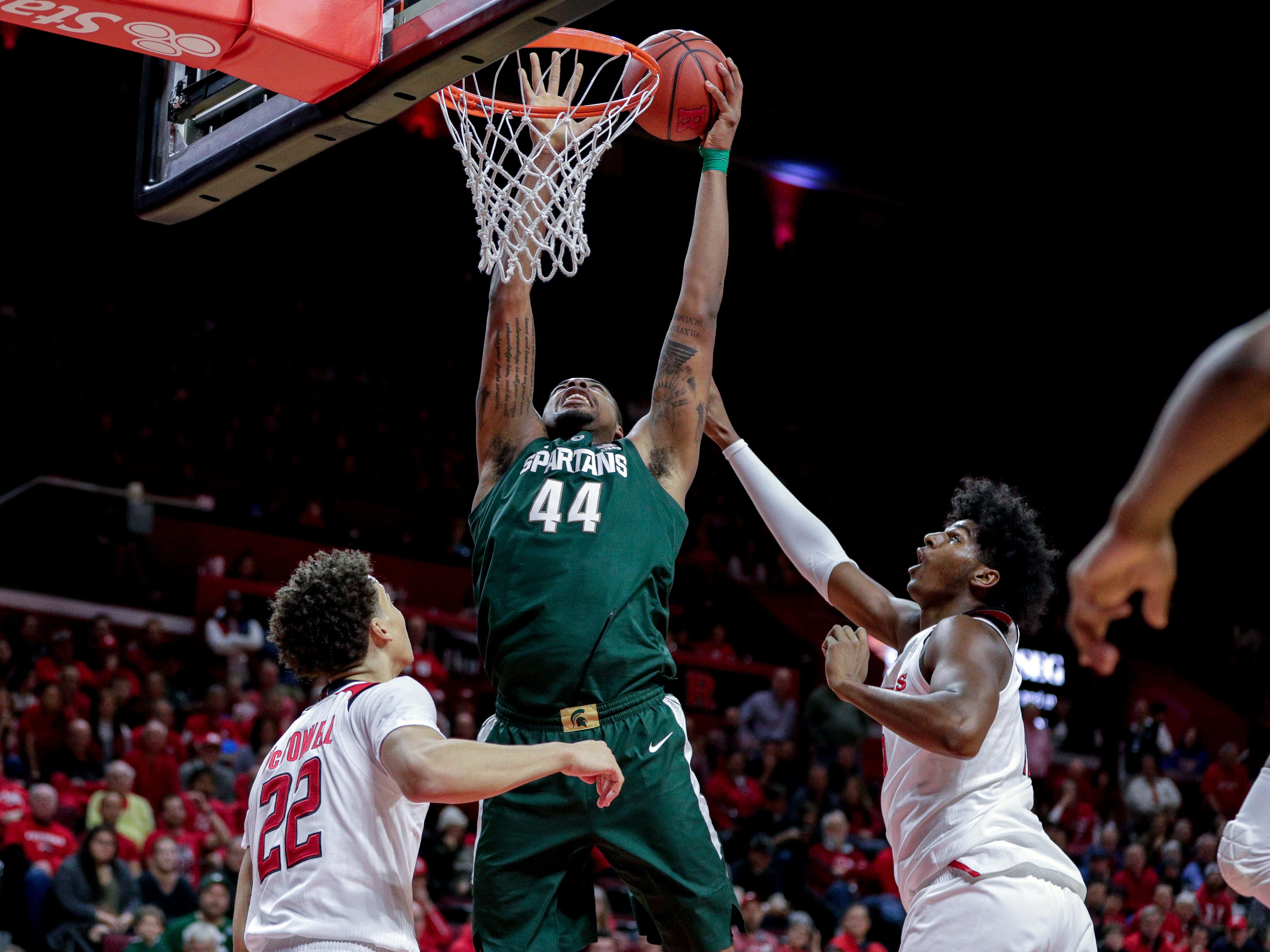 Michigan State Spartans forward Nick Ward (44) shoots the ball over Rutgers Scarlet Knights guard Caleb McConnell (22) and center Myles Johnson (15) during the first half at Rutgers Athletic Center (RAC).