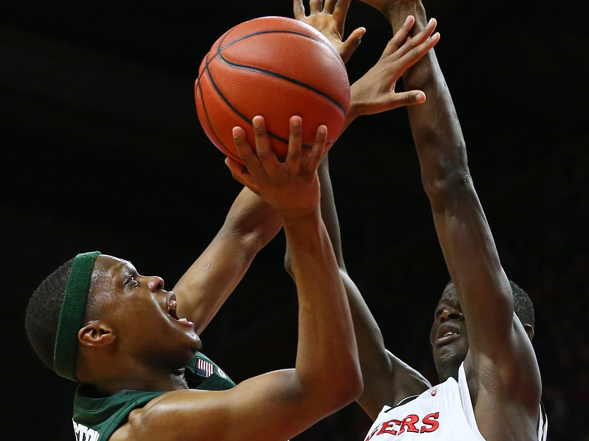 Cassius Winston #5 of the Michigan State Spartans is fouled by Eugene Omoruyi #5 of the Rutgers Scarlet Knights as he attempts a shot during the second half of a college basketball game at the Rutgers Athletic Center on November 30, 2018 in Piscataway, New Jersey. Michigan State defeated Rutgers 78-67.