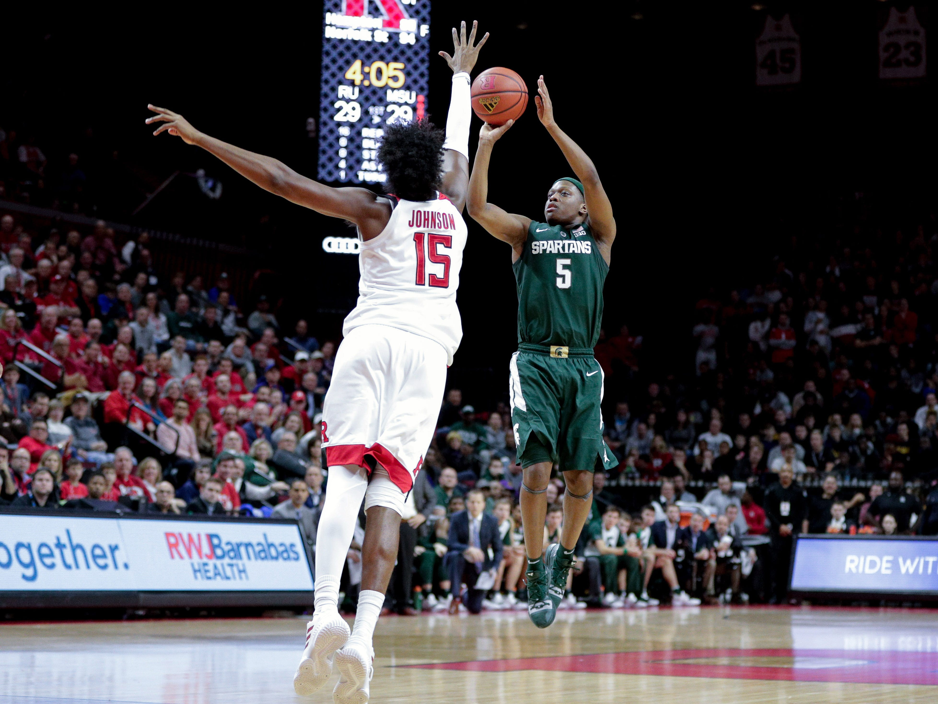 Michigan State Spartans guard Cassius Winston (5) shoots the ball as Rutgers Scarlet Knights center Myles Johnson (15) defends  during the first half at Rutgers Athletic Center (RAC).