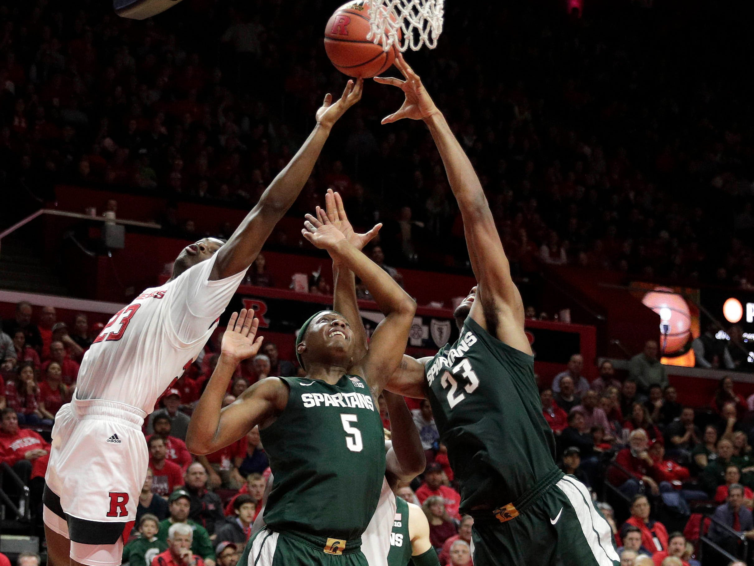 Rutgers Scarlet Knights guard Montez Mathis (23) rebounds against Michigan State Spartans guard Cassius Winston (5) and forward Xavier Tillman (23) during the second half at Rutgers Athletic Center (RAC).