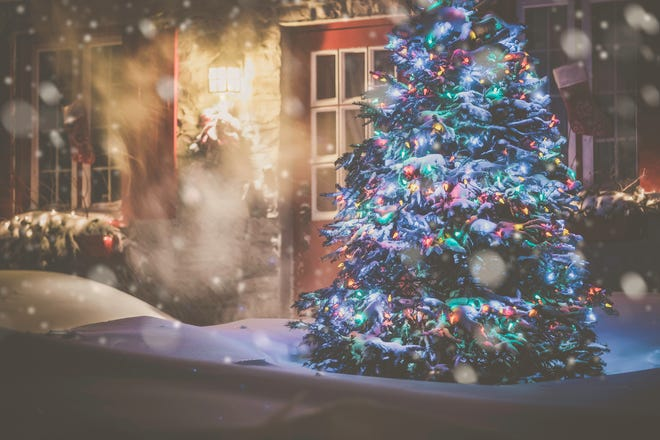 Illuminated Christmas Tree in front of a decorated home at Night During Snowstorm