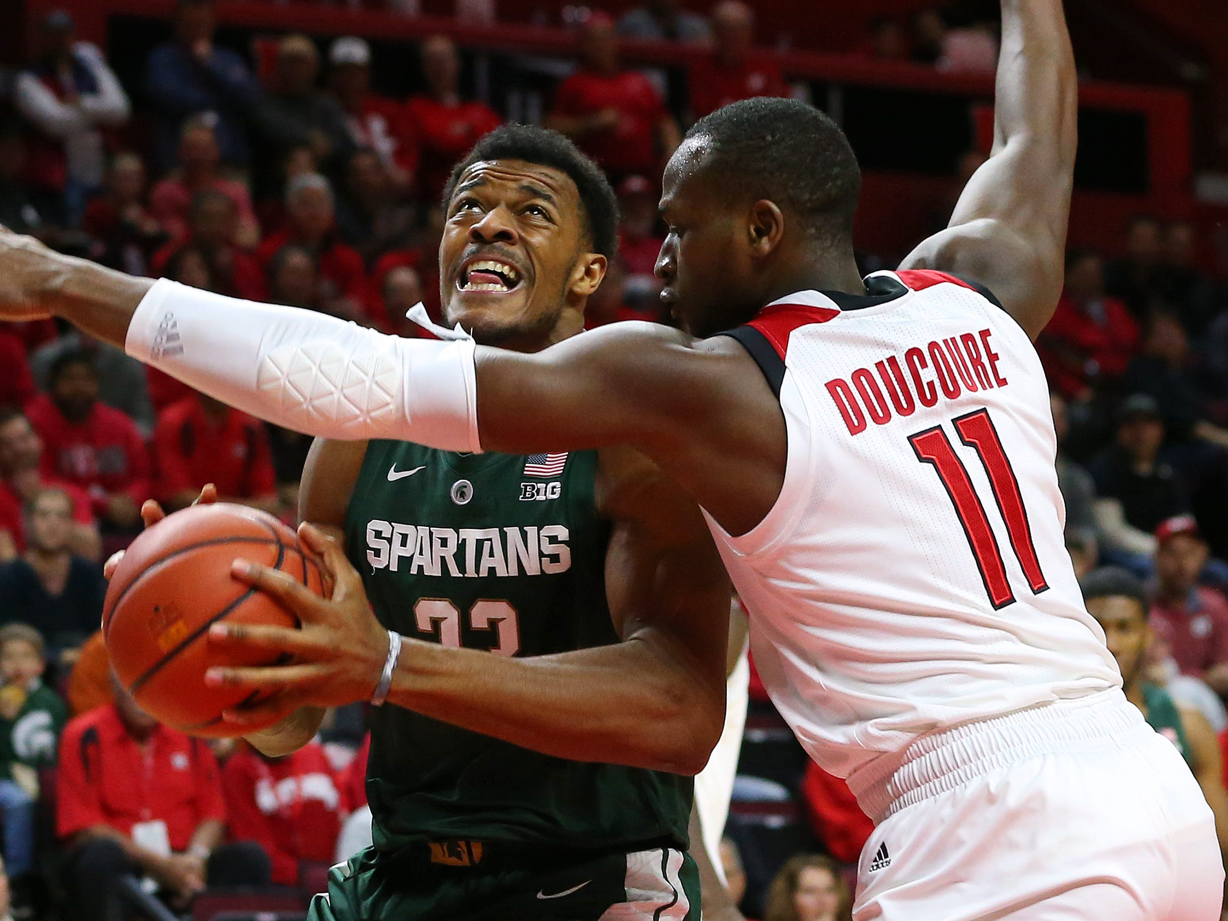 Xavier Tillman #23 of the Michigan State Spartans attempts to drive to the basket as Mamadou Doucoure #11 of the Rutgers Scarlet Knights defends during the first half of a college basketball game at the Rutgers Athletic Center on November 30, 2018 in Piscataway, New Jersey.