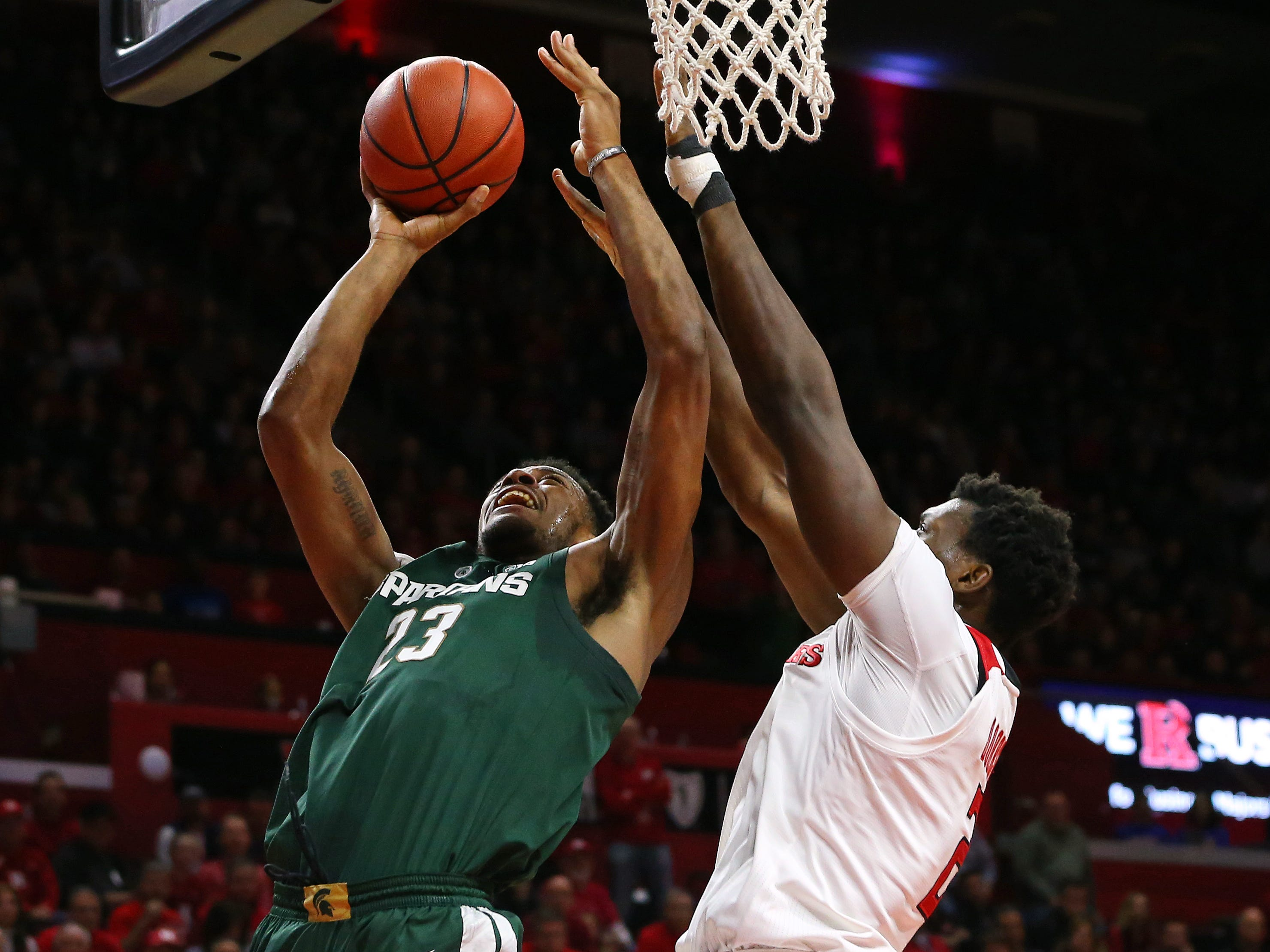 Xavier Tillman #23 of the Michigan State Spartans attempts a shot as Shaquille Doorson #2 of the Rutgers Scarlet Knights defends during the first half of a college basketball game at the Rutgers Athletic Center on November 30, 2018 in Piscataway, New Jersey.