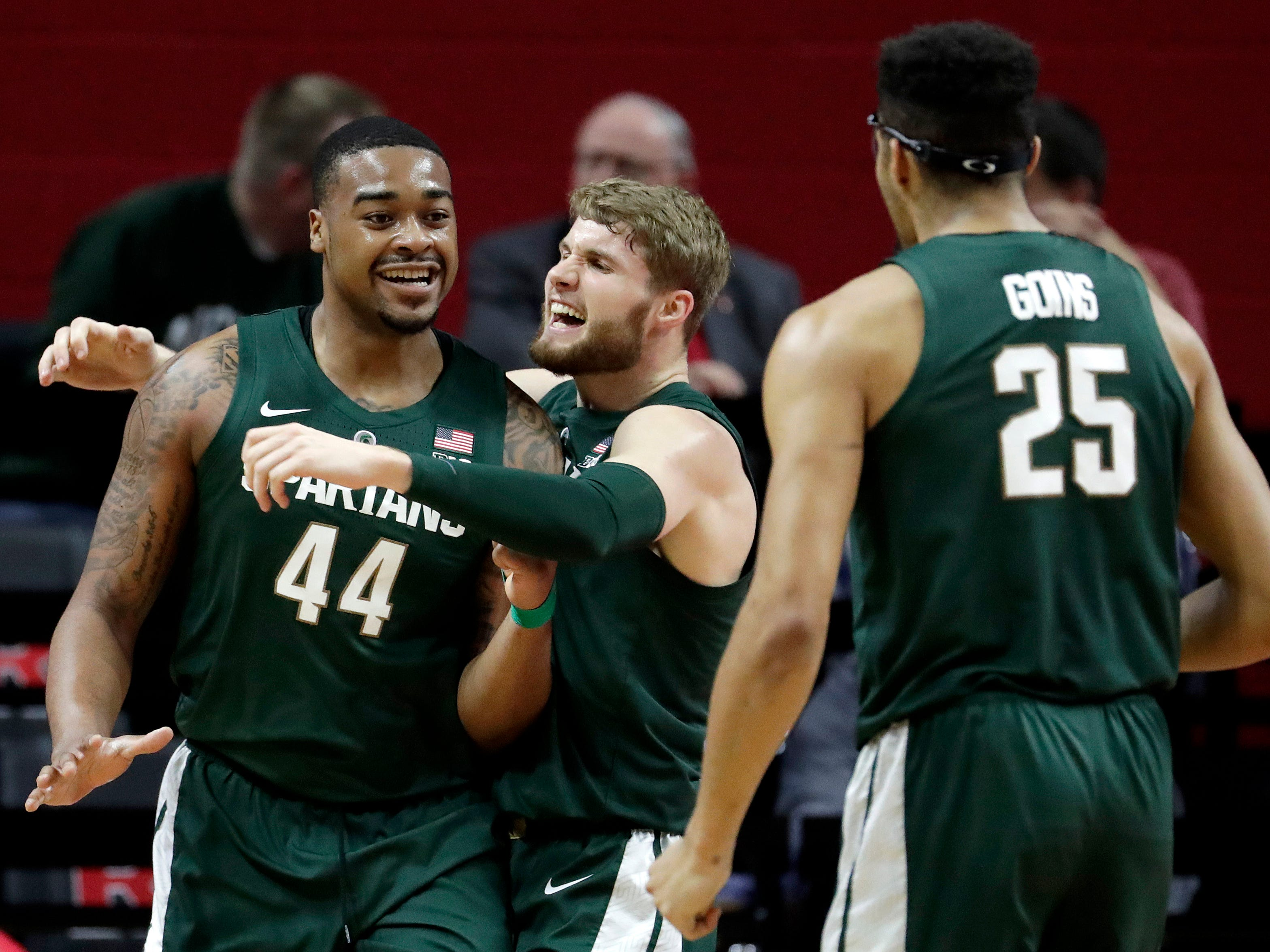 Michigan State forward Nick Ward (44) is hugged by Kyle Ahrens after scoring a basket against Rutgers during the first half of an NCAA college basketball game, Friday, Nov. 30, 2018, in Piscataway, N.J.