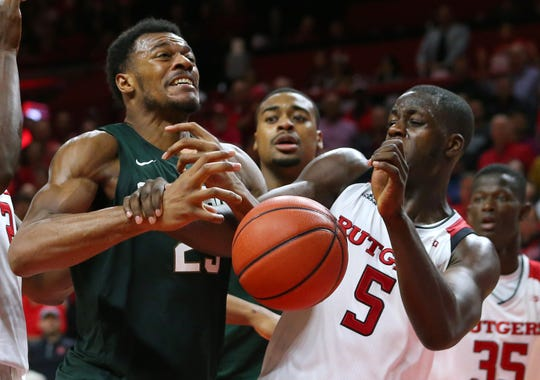 Xavier Tillman #23 of the Michigan State Spartans is fouled by Eugene Omoruyi #5 of the Rutgers Scarlet Knights during the second half of a college basketball game at the Rutgers Athletic Center on November 30, 2018 in Piscataway, New Jersey. Michigan State defeated Rutgers 78-67.