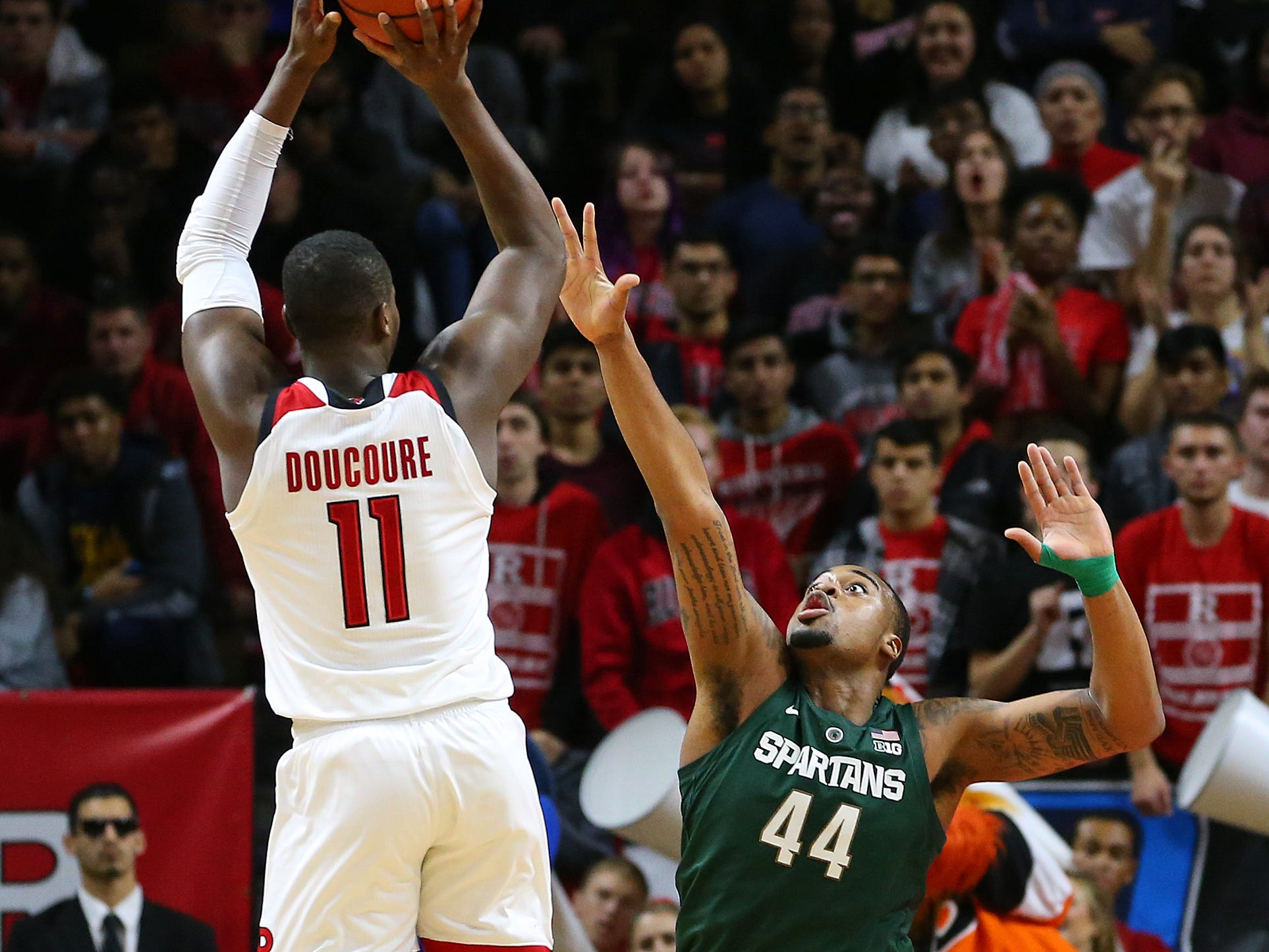 Mamadou Doucoure #11 of the Rutgers Scarlet Knights attempts a shot as Nick Ward #44 of the Michigan State Spartans defends during the first half of a college basketball game at the Rutgers Athletic Center on November 30, 2018 in Piscataway, New Jersey.
