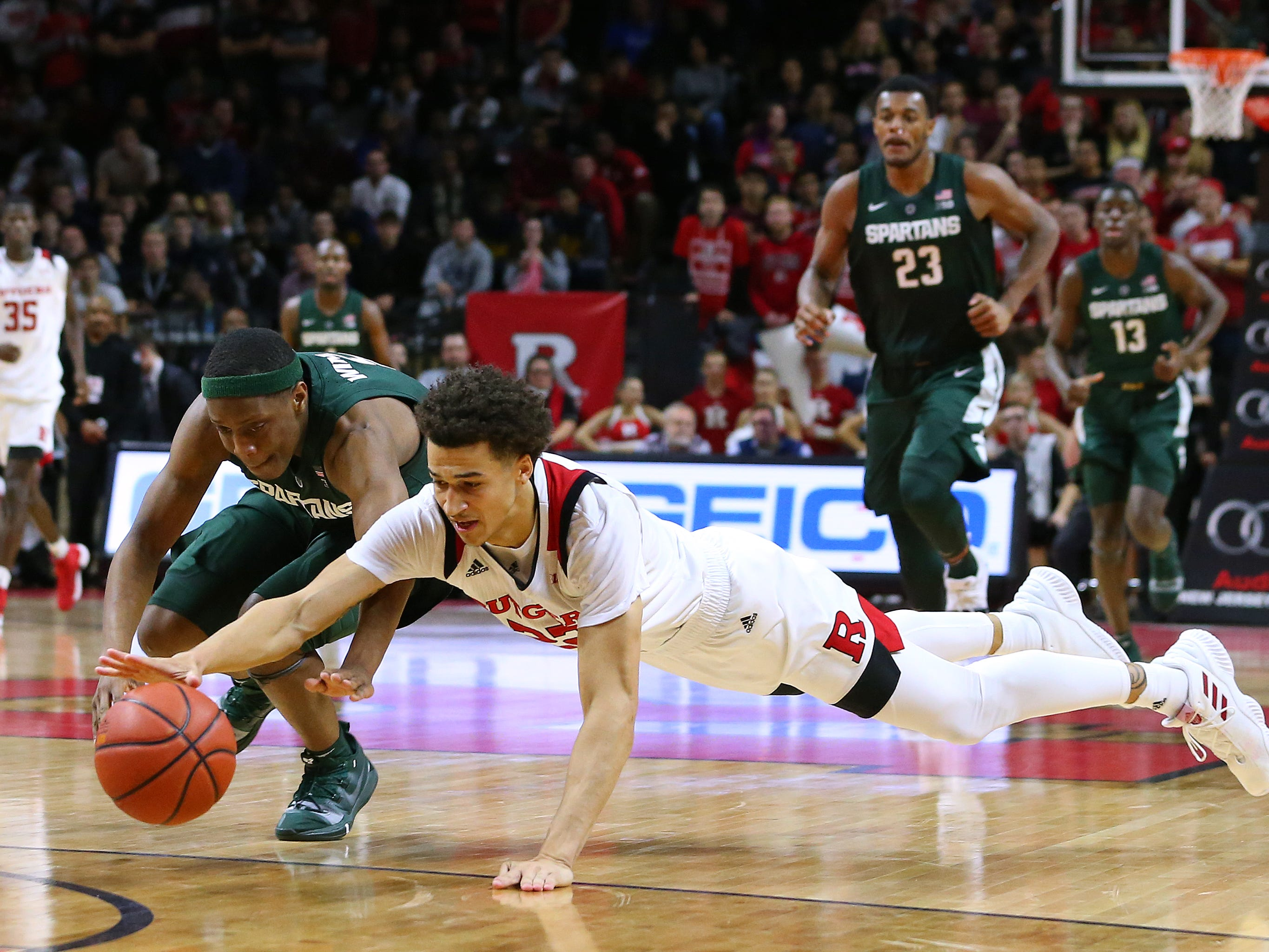 Caleb McConnell #22 of the Rutgers Scarlet Knights dives for a loose ball along with Cassius Winston #5 of the Michigan State Spartans during the first half of a college basketball game at the Rutgers Athletic Center on November 30, 2018 in Piscataway, New Jersey.