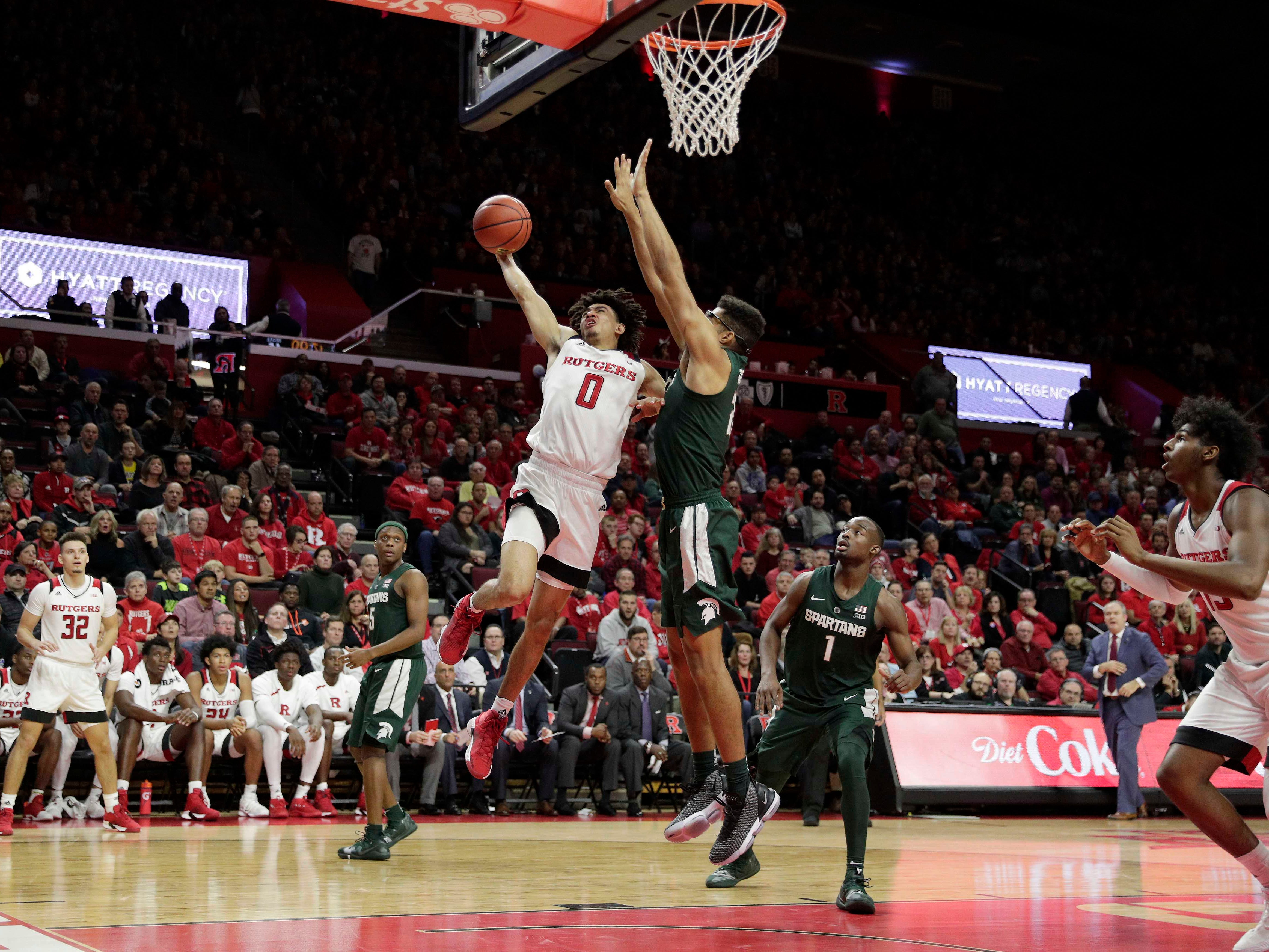 Rutgers Scarlet Knights guard Geo Baker (0) drives to the basket as Michigan State Spartans guard Matt McQuaid (20) defends during the second half at Rutgers Athletic Center (RAC).