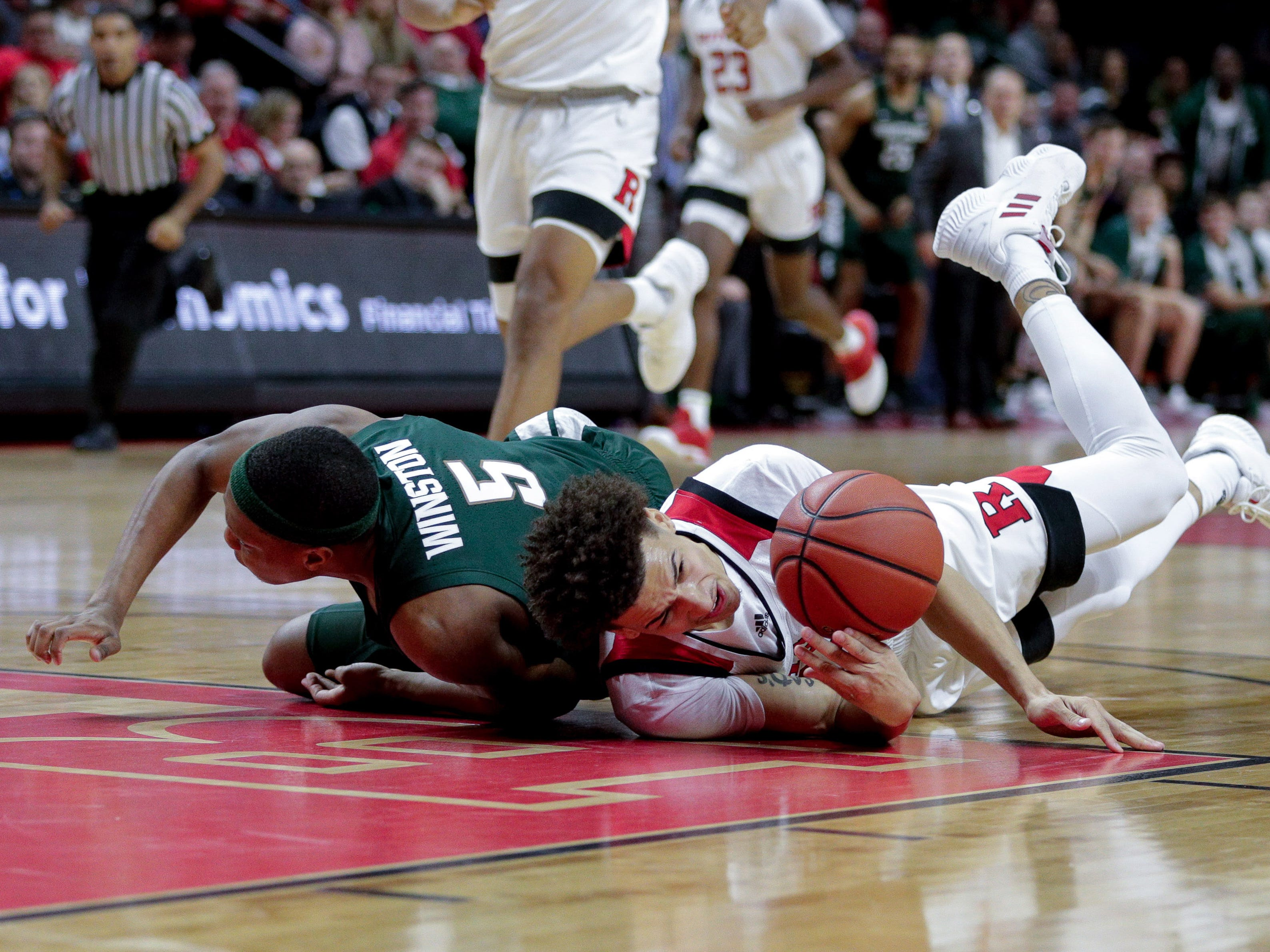Michigan State Spartans guard Cassius Winston (5) battles for the ball against Rutgers Scarlet Knights guard Caleb McConnell (22) during the first half at Rutgers Athletic Center (RAC).