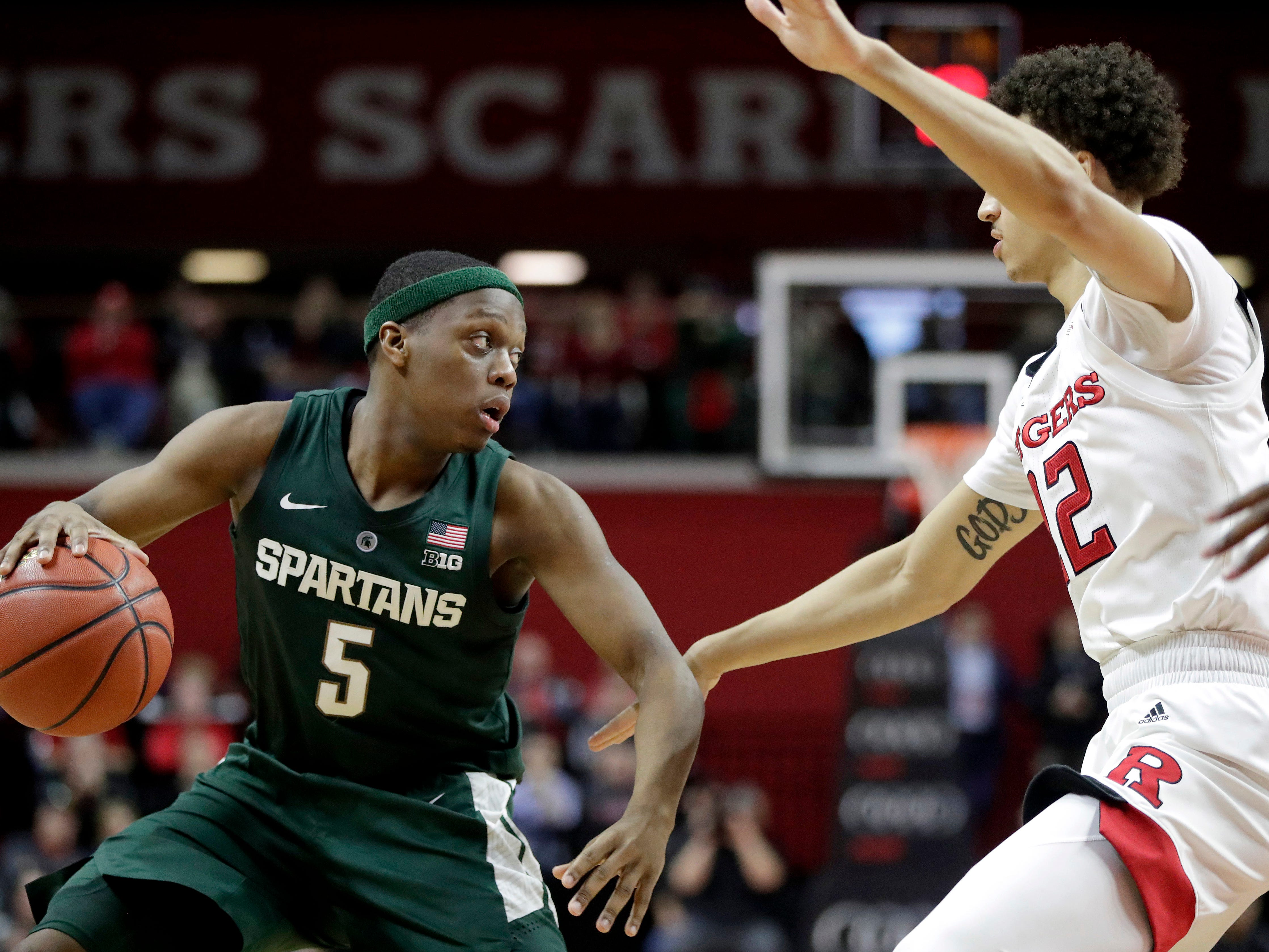 Michigan State guard Cassius Winston, left, drives against Rutgers guard Caleb McConnell during the second half of an NCAA college basketball game, Friday, Nov. 30, 2018, in Piscataway, N.J.