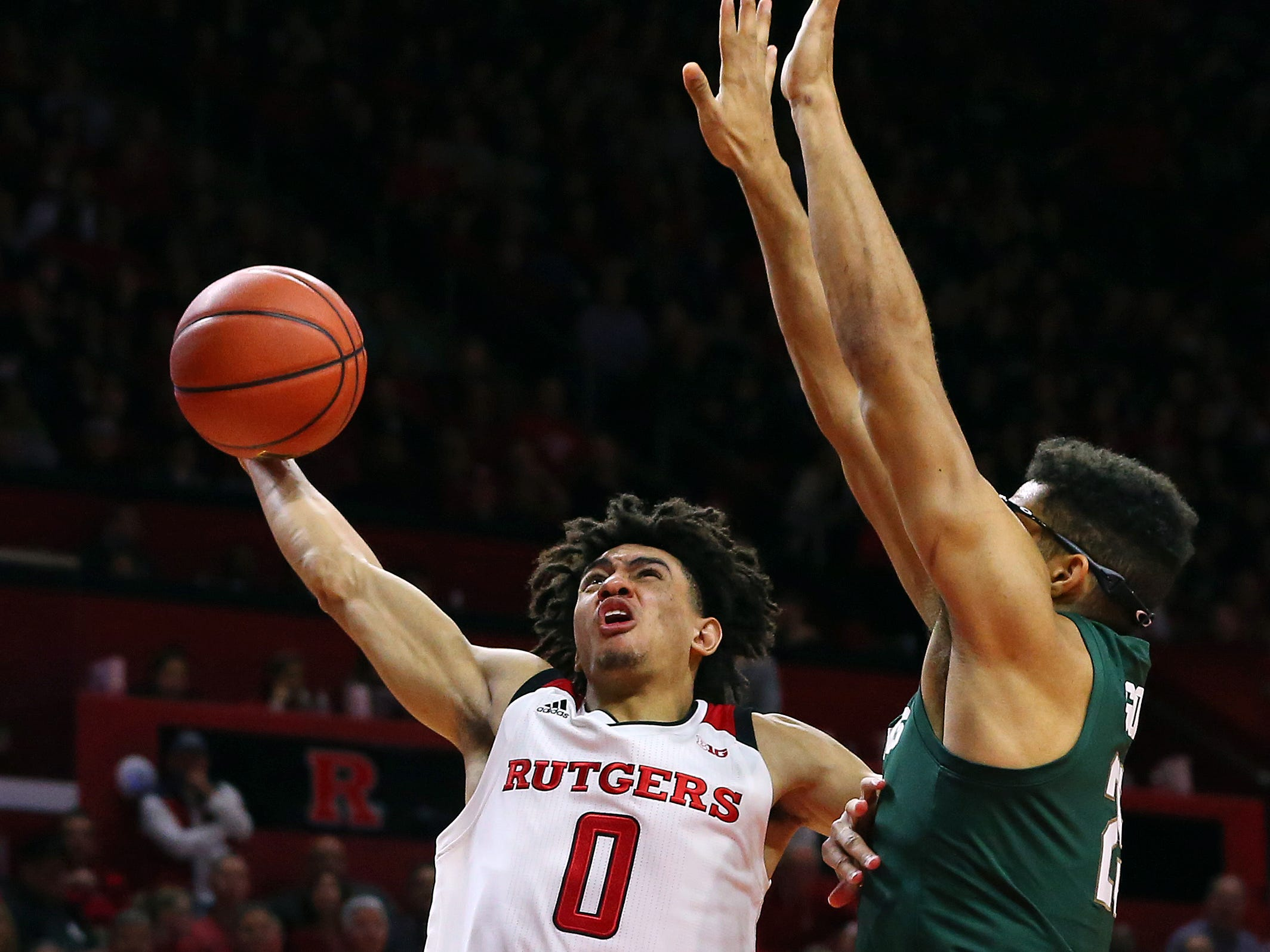 Geo Baker #0 of the Rutgers Scarlet Knights attempts a shot as Kenny Goins #25 of the Michigan State Spartans defends during the second half of a college basketball game at the Rutgers Athletic Center on November 30, 2018 in Piscataway, New Jersey. Michigan State defeated Rutgers 78-67.