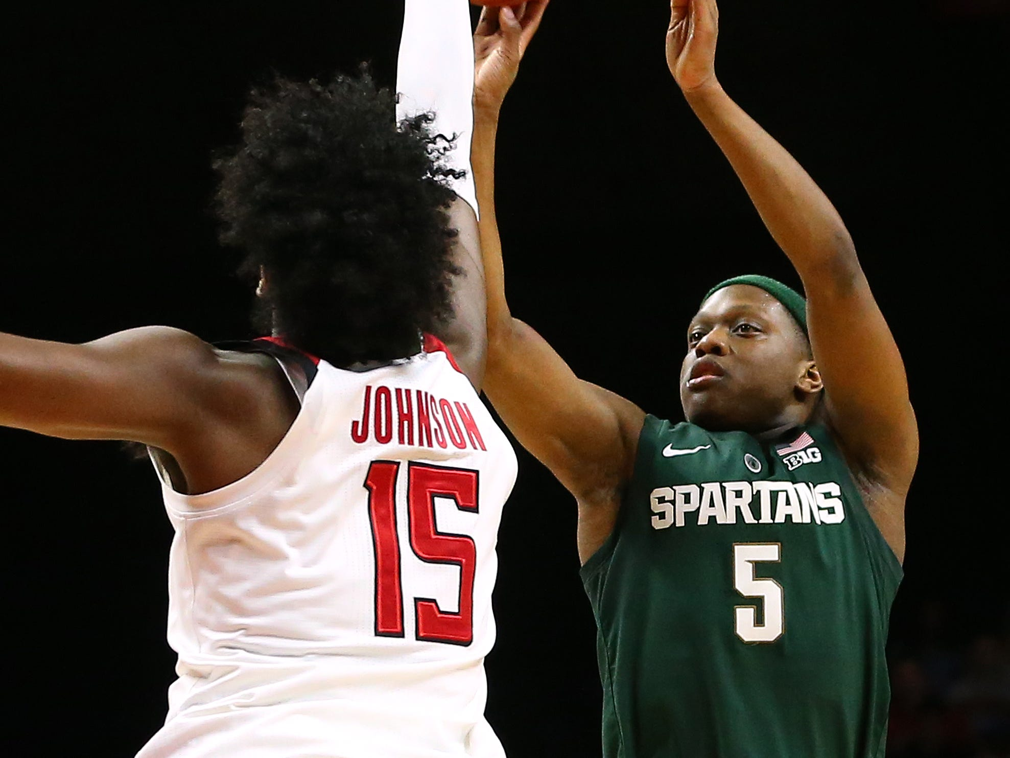 Cassius Winston #5 of the Michigan State Spartans attempts a shot as Myles Johnson #15 of the Rutgers Scarlet Knights defends during the first half of a college basketball game at the Rutgers Athletic Center on November 30, 2018 in Piscataway, New Jersey.