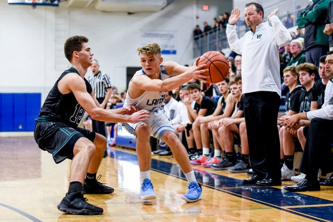 Williamston's Mitchell Cook, left, pressures Lansing Catholic's Alex Watters during the second quarter on Friday, Nov. 30, 2018, at Lansing Catholic High School.