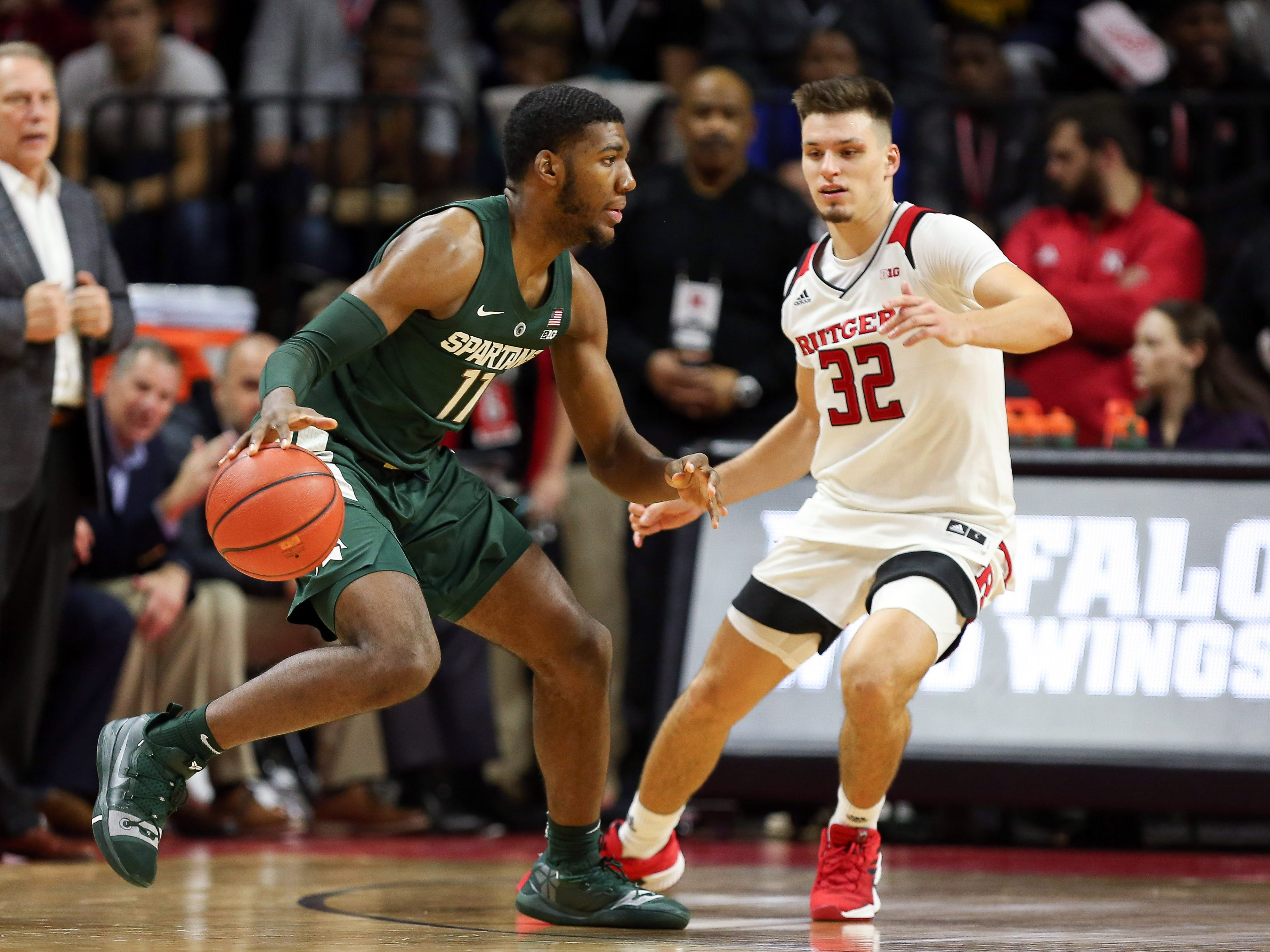 Michigan State Spartans forward Aaron Henry (11) dribbles as Rutgers Scarlet Knights guard Peter Kiss (32) defends in front of  head coach Tom Izzo during the second half at Rutgers Athletic Center (RAC).