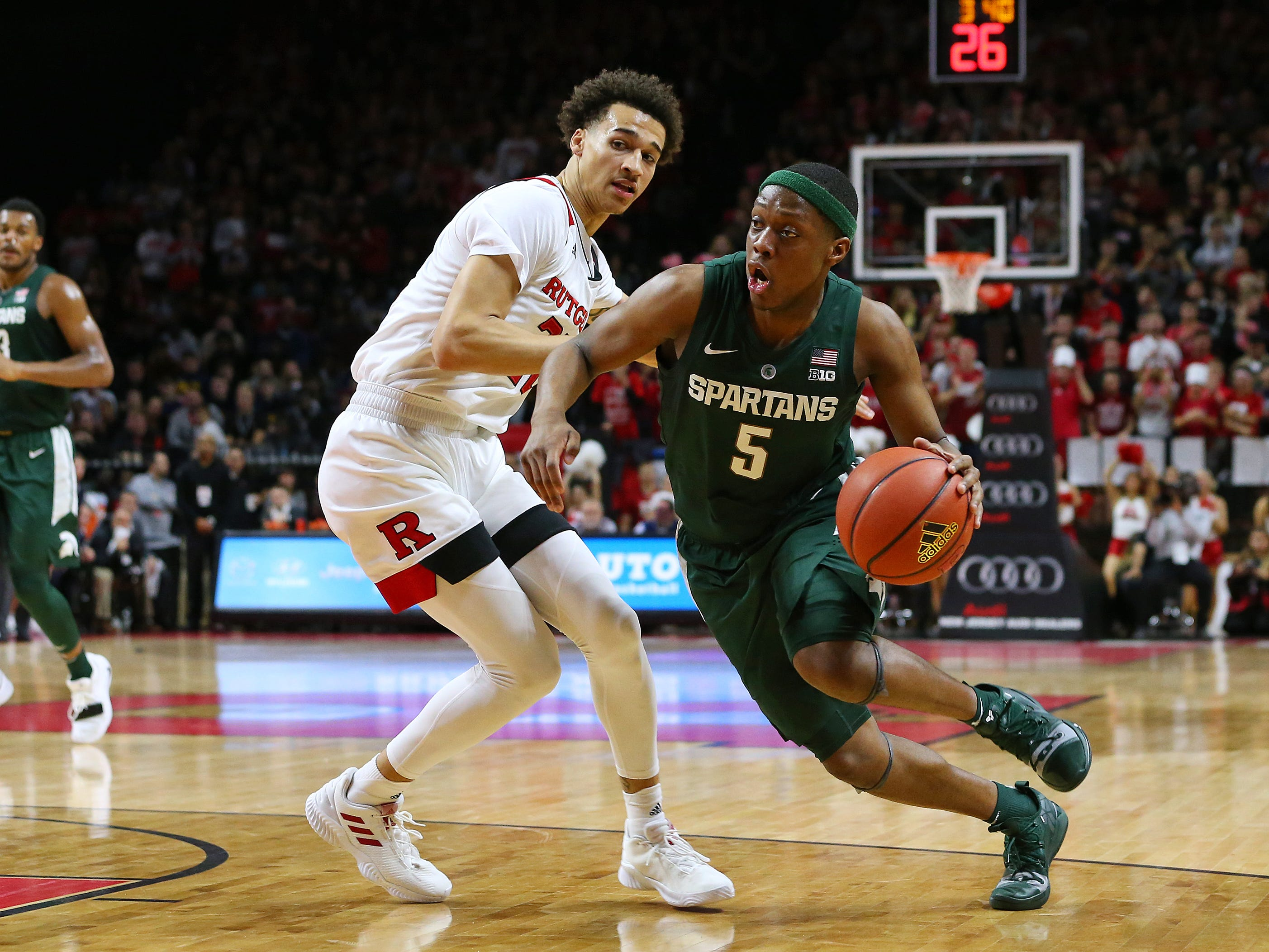 Cassius Winston #5 of the Michigan State Spartans drives to the basket as Caleb McConnell #22 of the Rutgers Scarlet Knights defends during the second half of a college basketball game at the Rutgers Athletic Center on November 30, 2018 in Piscataway, New Jersey. Michigan State defeated Rutgers 78-67.