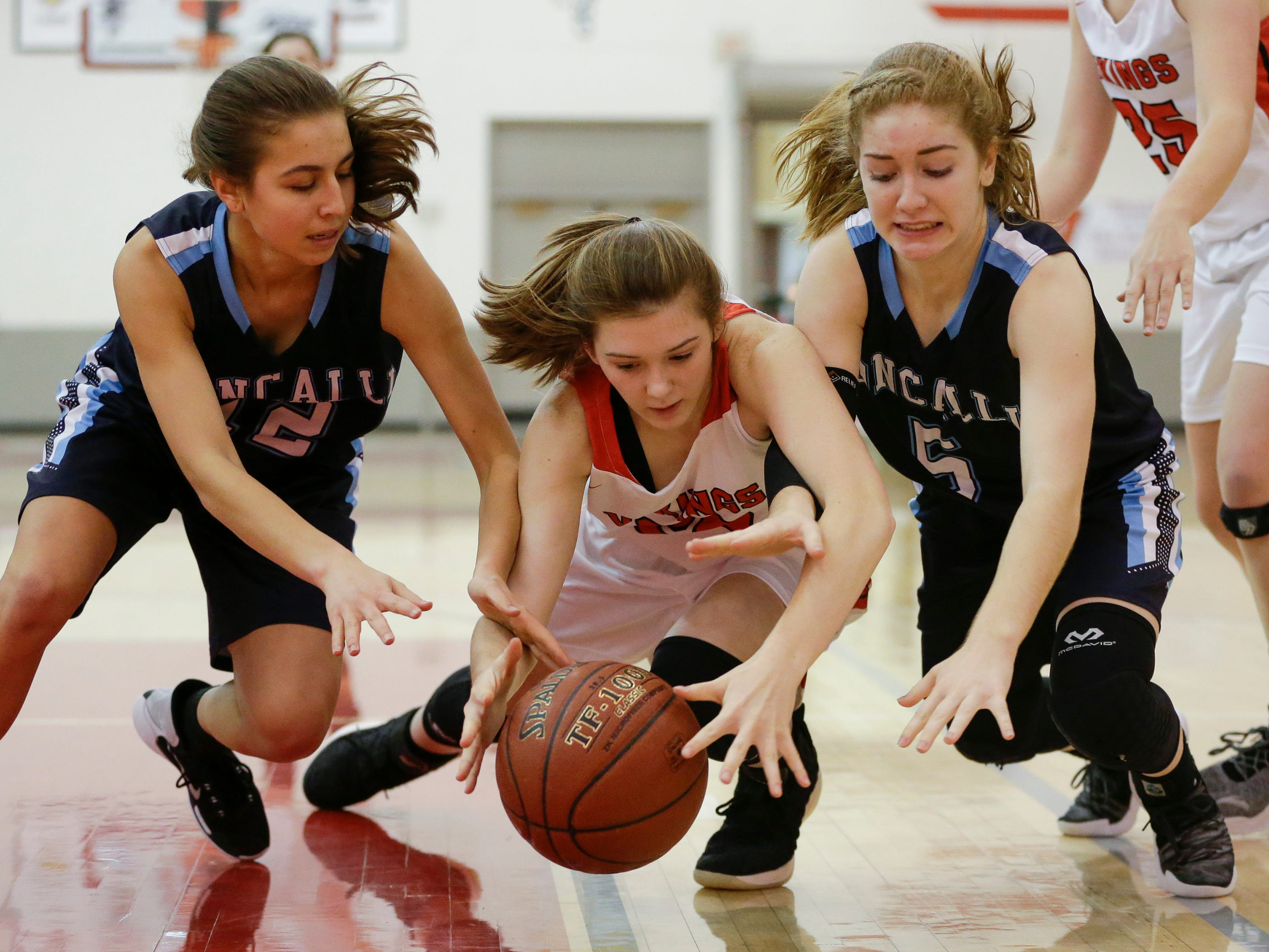 Valders' Kate Wagner (20) fends off Roncalli's Megan Moczynski, left, and Morgan Pritzl for possession of a loose ball during an Eastern Wisconsin Conference game at Valders High School Friday, November 30, 2018, in Valders, Wis. Joshua Clark/USA TODAY NETWORK-Wisconsin