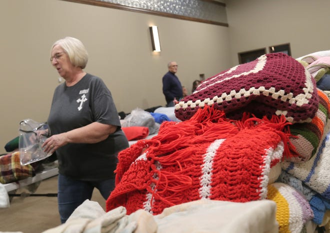 Sue Noblet of Reaching Out Ministries helps organize items during the blanket drive at Crossroads City Center in Mansfield on Saturday. It was estimated that over 50 people came in that morning to receive blankets.