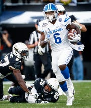 Memphis running back Patrick Taylor Jr. (right) scrambles past the UCF defense for a touchdown during action at the AAC Championship Football game Saturday, December 1, 2018 in Orlando.