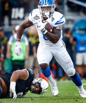 Memphis running back Patrick Taylor Jr., right, scrambles past the UCF defense during action at the AAC championship game Dec. 1, 2018, in Orlando, Fla.