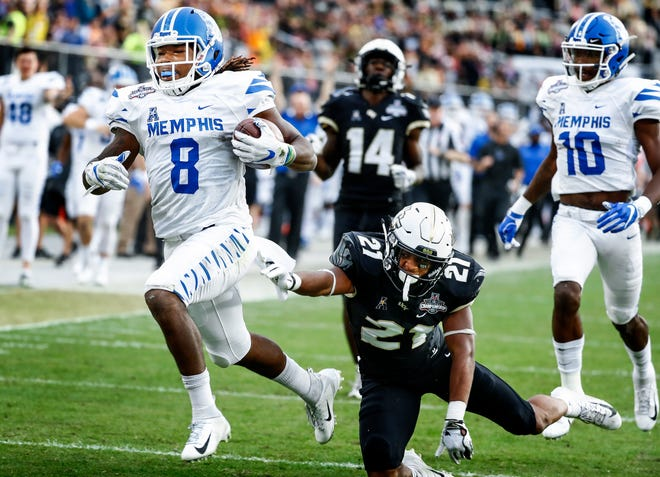Memphis running back Darrell Henderson (left) scrambles past the UCF defender Rashard Causey (middle) for a touchdown during action at the AAC Championship Football game Saturday, December 1, 2018 in Orlando.