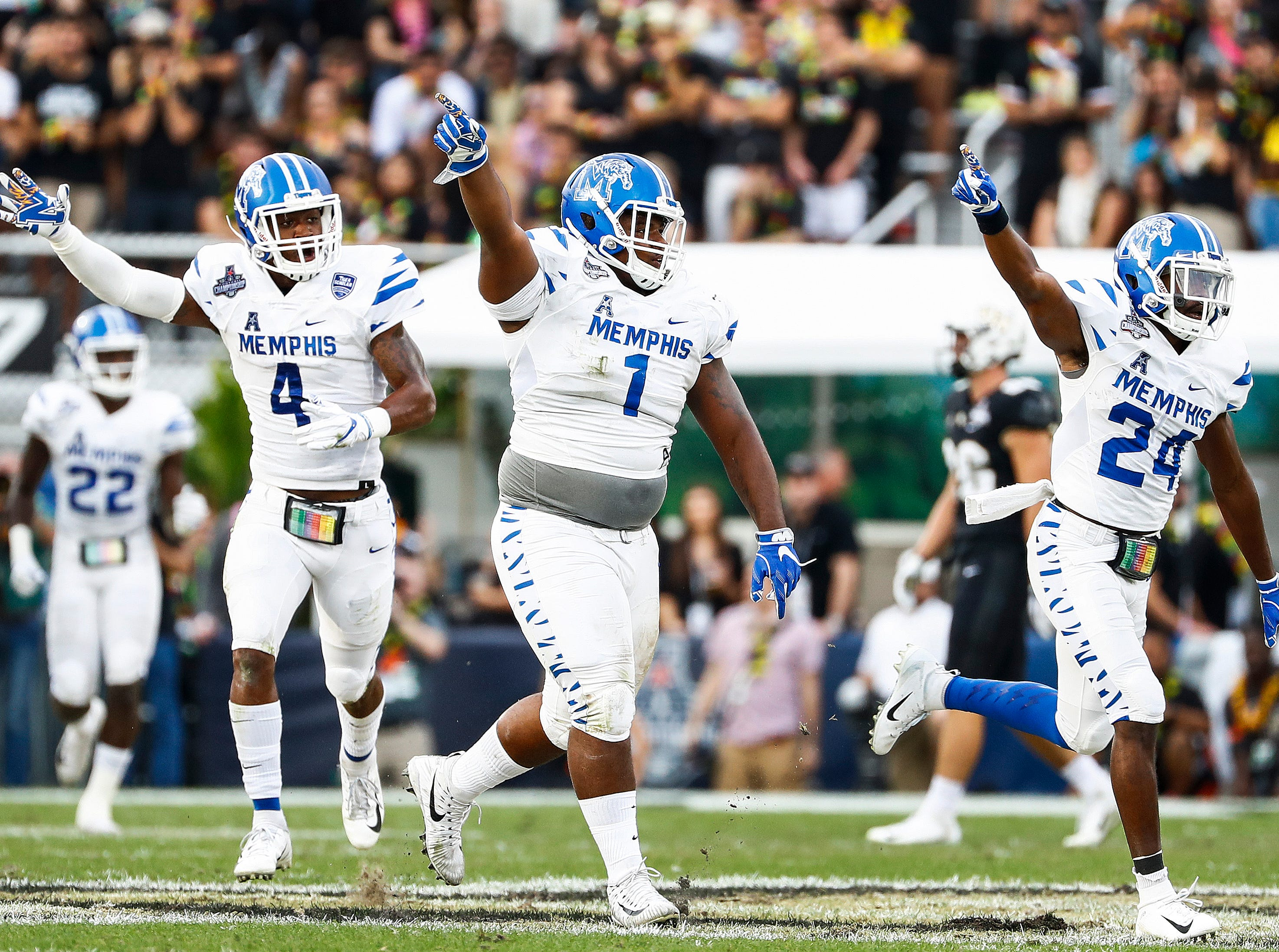 Memphis defenders (left to right) Josh Perry, O'Bryan Goodson and Tito Windham celebrate a fumble recovery against UCF during action at the AAC Championship Football game Saturday, December 1, 2018 in Orlando.