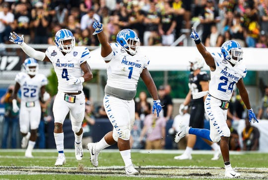 Memphis defenders (from left) Josh Perry, O'Bryan Goodson and Tito Windham celebrate a fumble recovery against Central Florida during the AAC championship game last season.