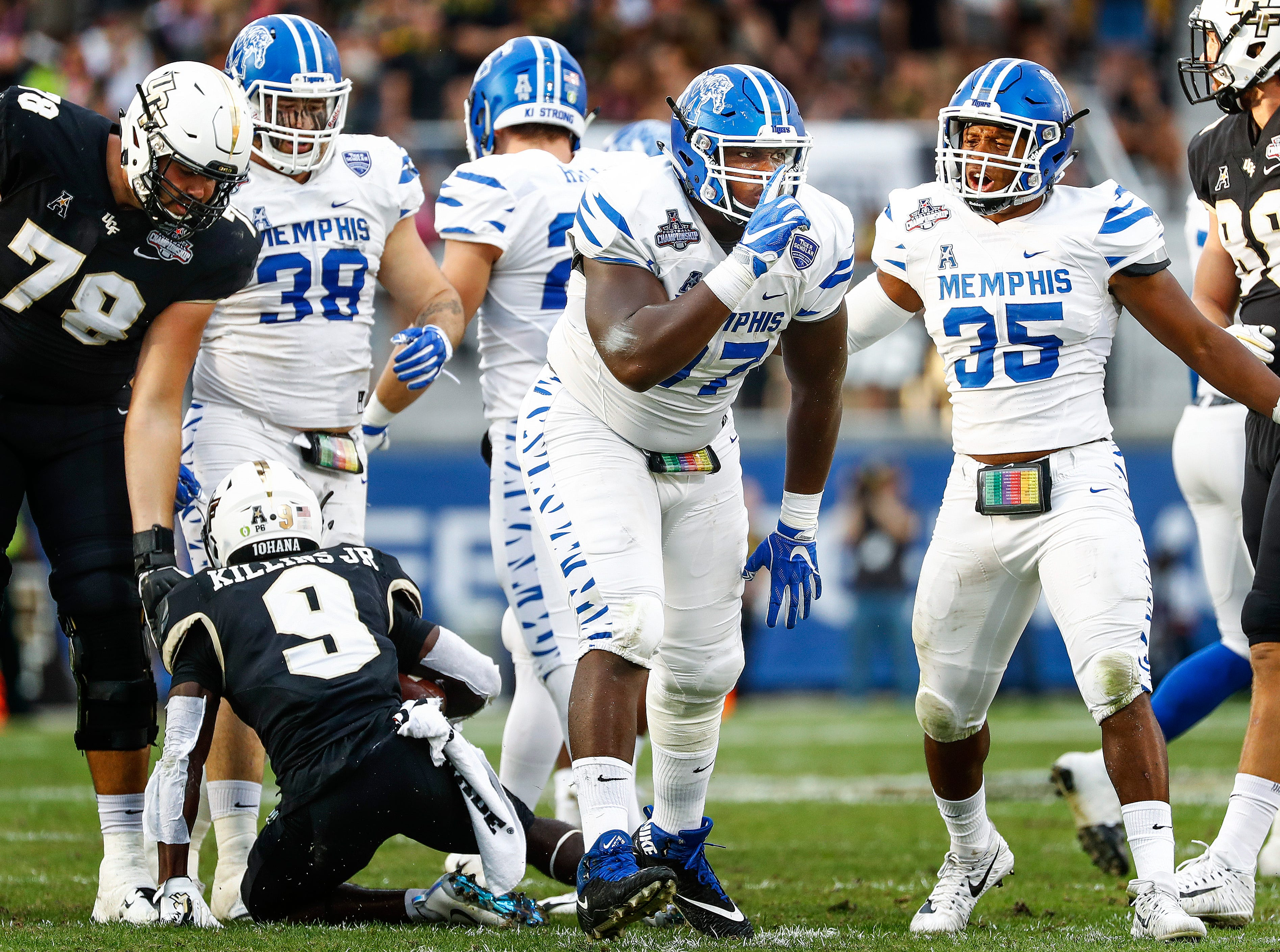 Memphis defender Emmanuel Cooper (middle) celebrates a tackle for a loss against UCF during action at the AAC Championship Football game Saturday, December 1, 2018 in Orlando.