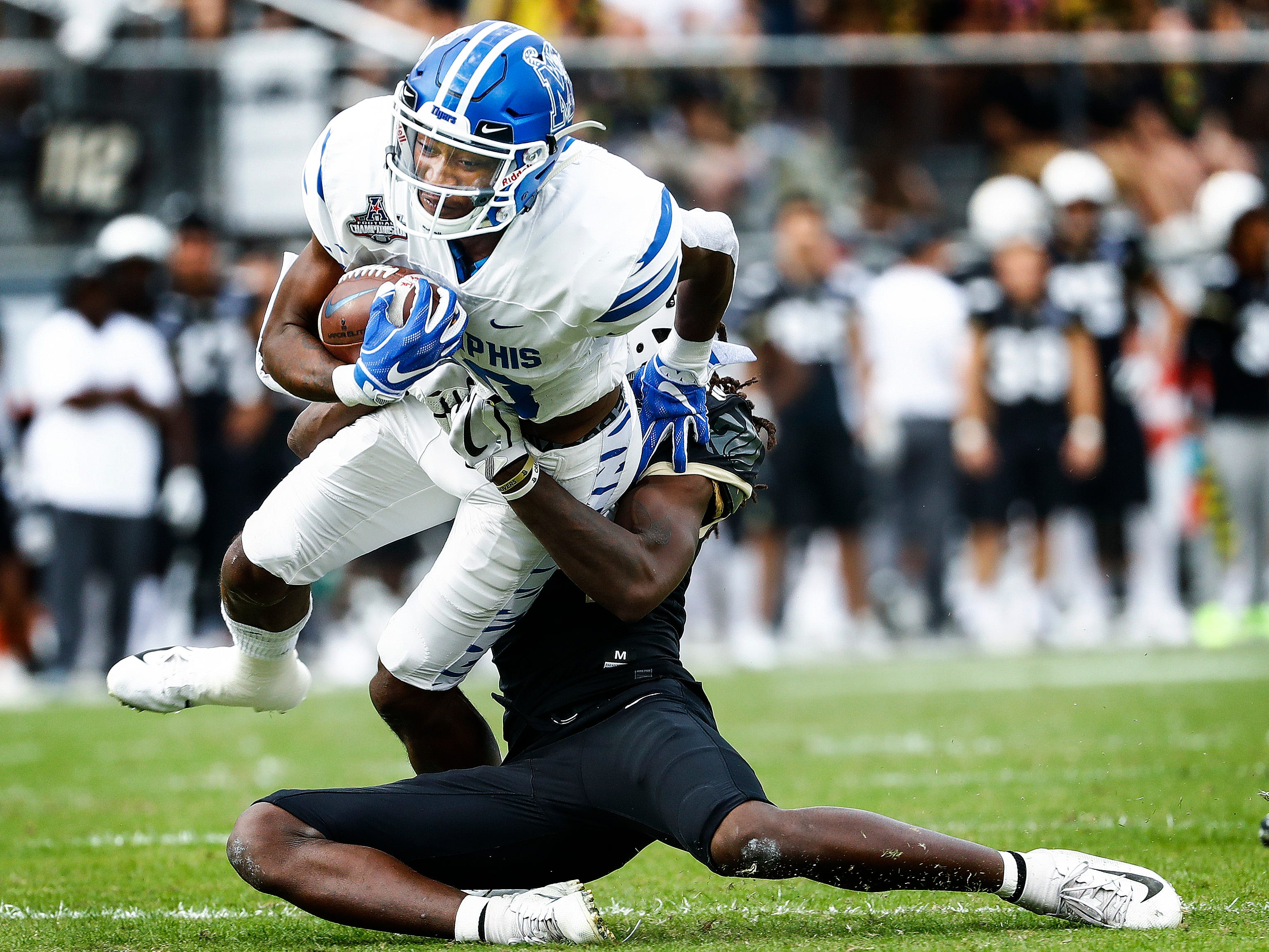 Memphis receiver Damonte Coxie (left) fights for positive yards against the UCF defense during action at the AAC Championship Football game Saturday, December 1, 2018 in Orlando.